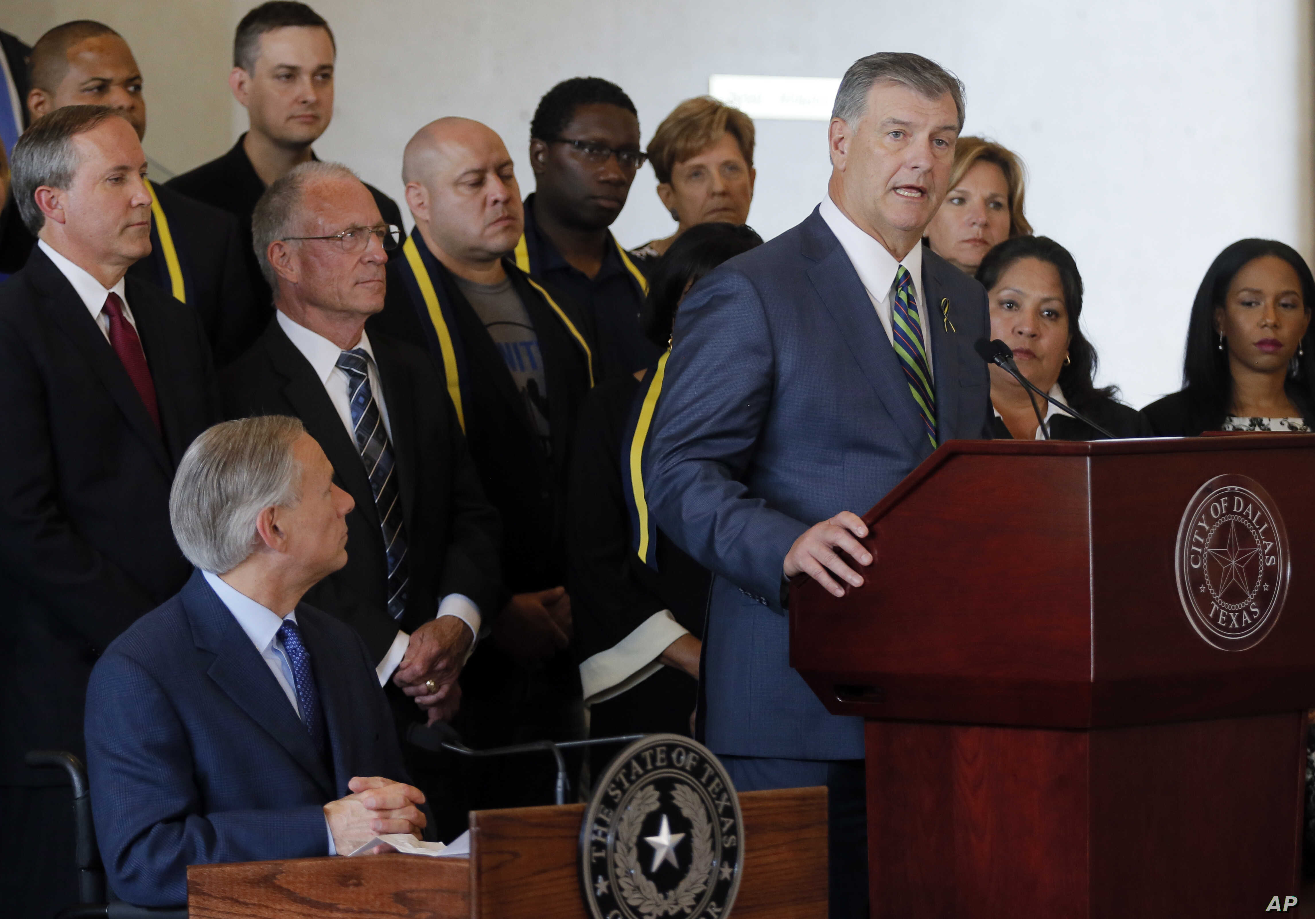Texas Governor Greg Abbott, lower left, listens as Dallas Mayor Mike Rawlings, right, address the media during a news conference at city hall, in Dallas, July 8, 2016.