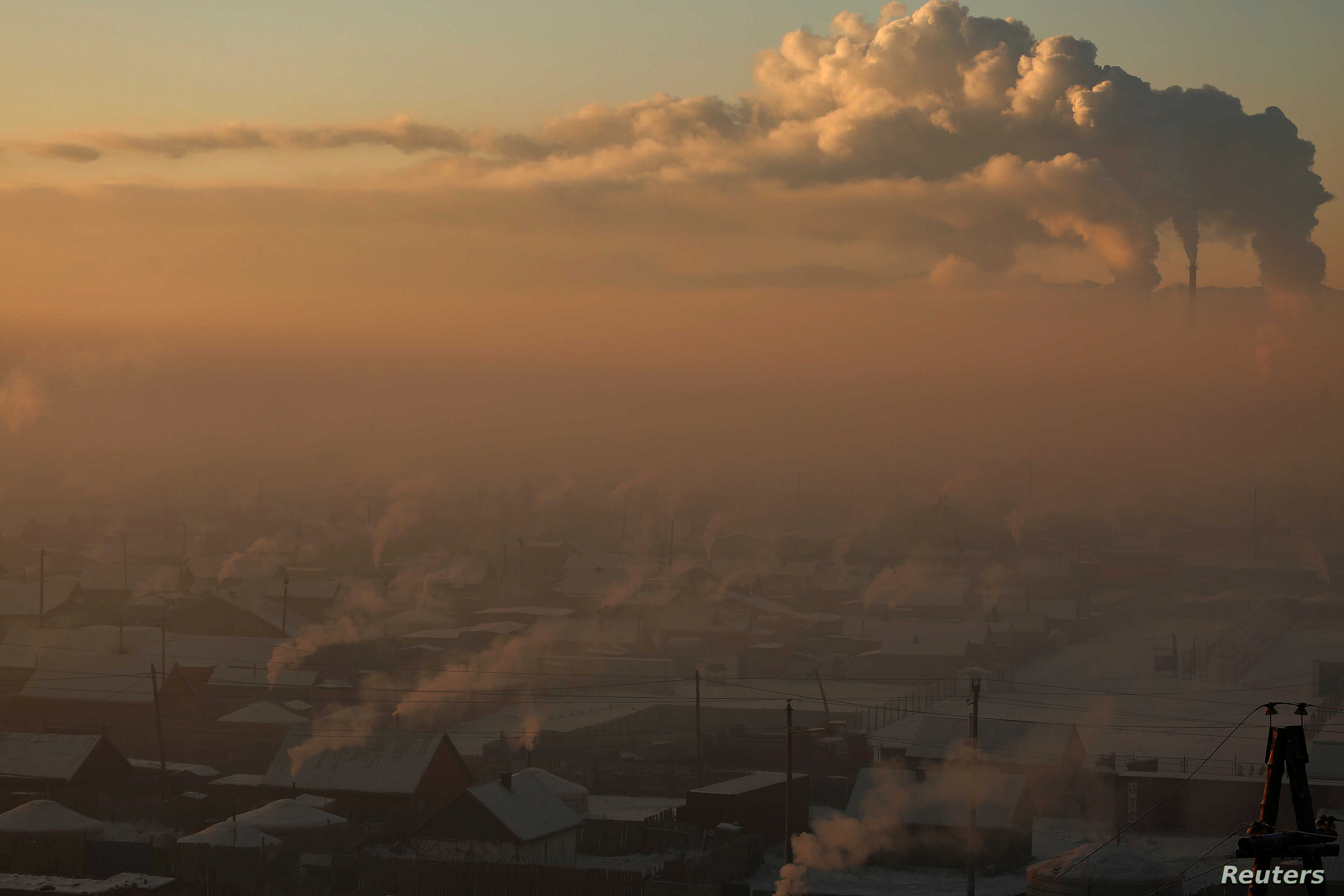 Power plant chimneys stand behind a coal burning neighborhood covered in a thick haze on the outskirts of Ulaanbaatar, Mongolia, Jan. 19, 2017.