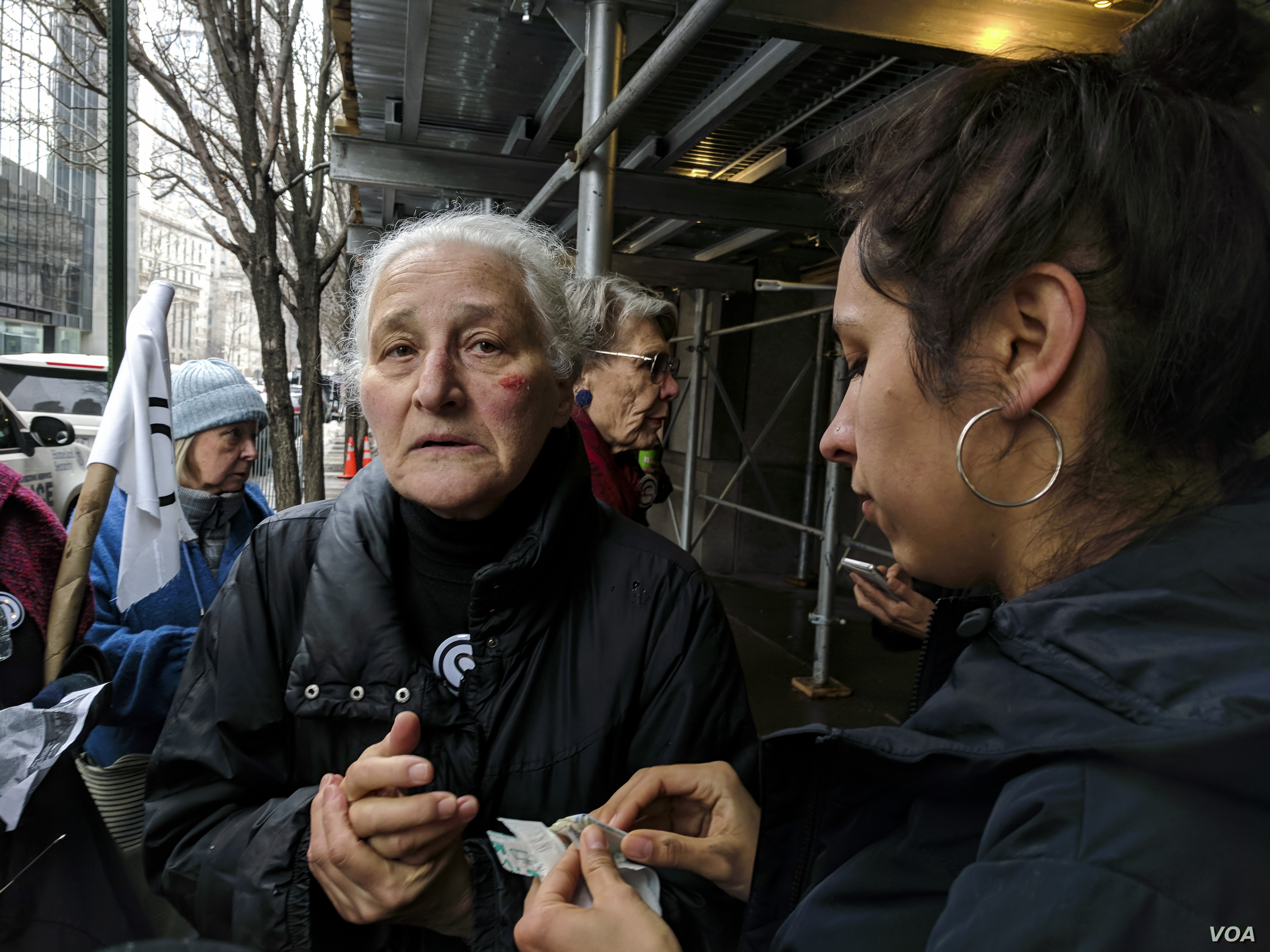 Barbara Moore, 81, tends to her wounds after a scuffle broke out between activists and police outside New York's immigration court, following news that Ravi Ragbir, a well-known immigrant-rights activist, had been detained. (R. Taylor/VOA)
