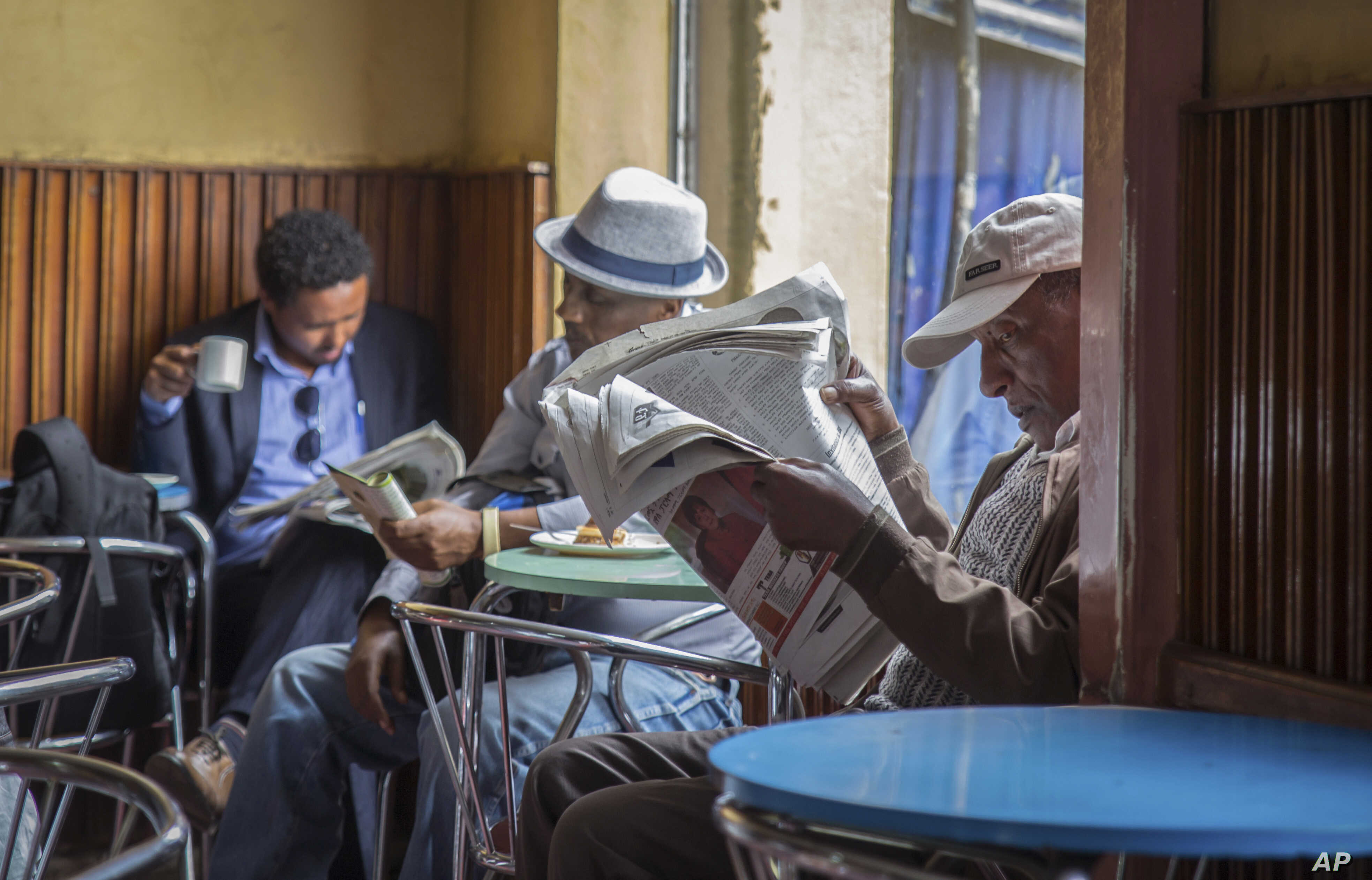 FILE - In this Oct. 10, 2016 file photo, Ethiopian men read newspapers and drink coffee at a cafe during a declared state of emergency in Addis Ababa, Ethiopia. Since 2015 there have been wide-ranging internet shutdowns.