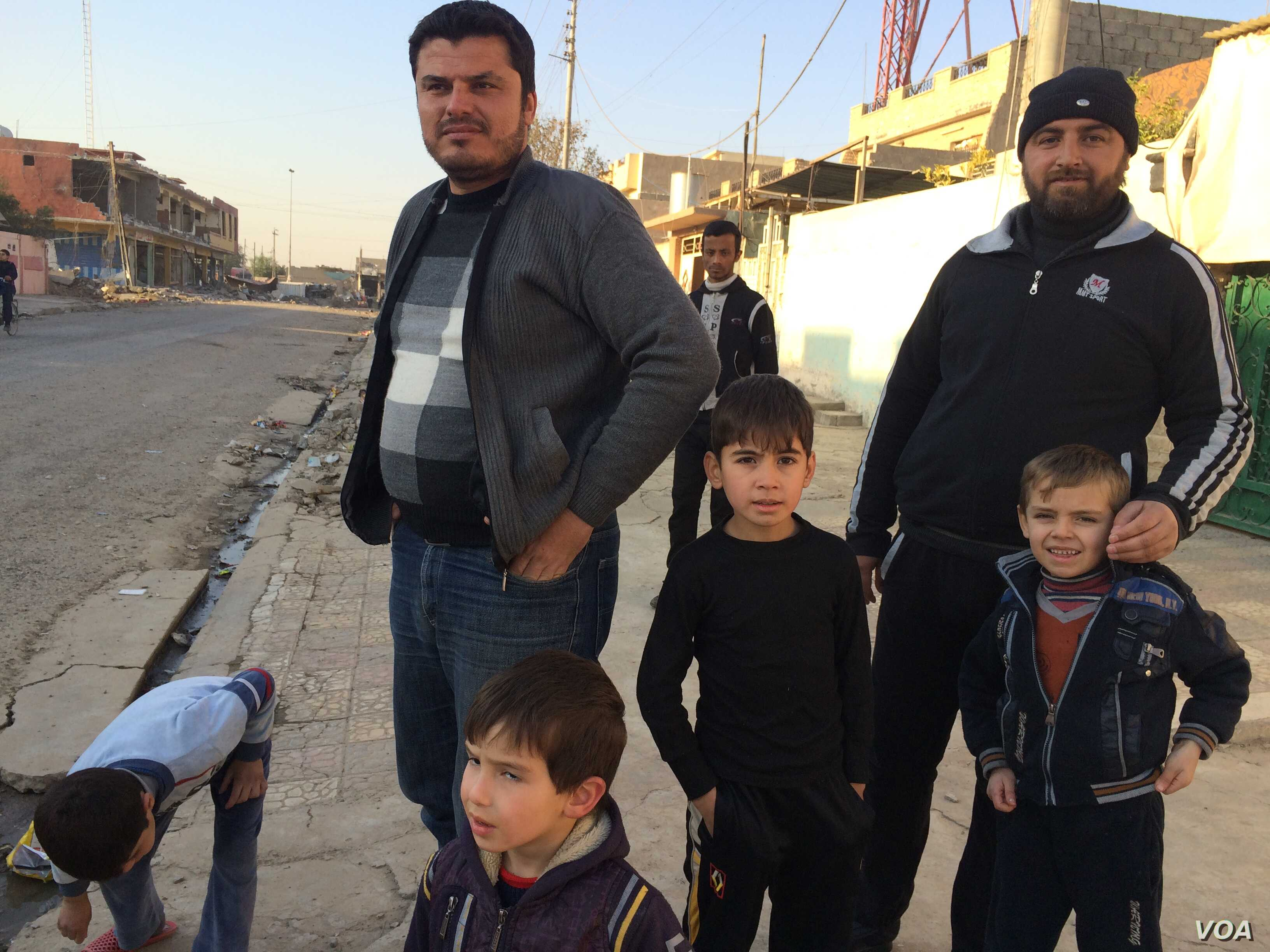 Arabic language teacher Nathir Bashir and his family stand outside their Mosul home as mortars and gunfire can be heard in the next neighborhood in Mosul, Iraq, Nov. 27, 2016. (H. Murdock/VOA)