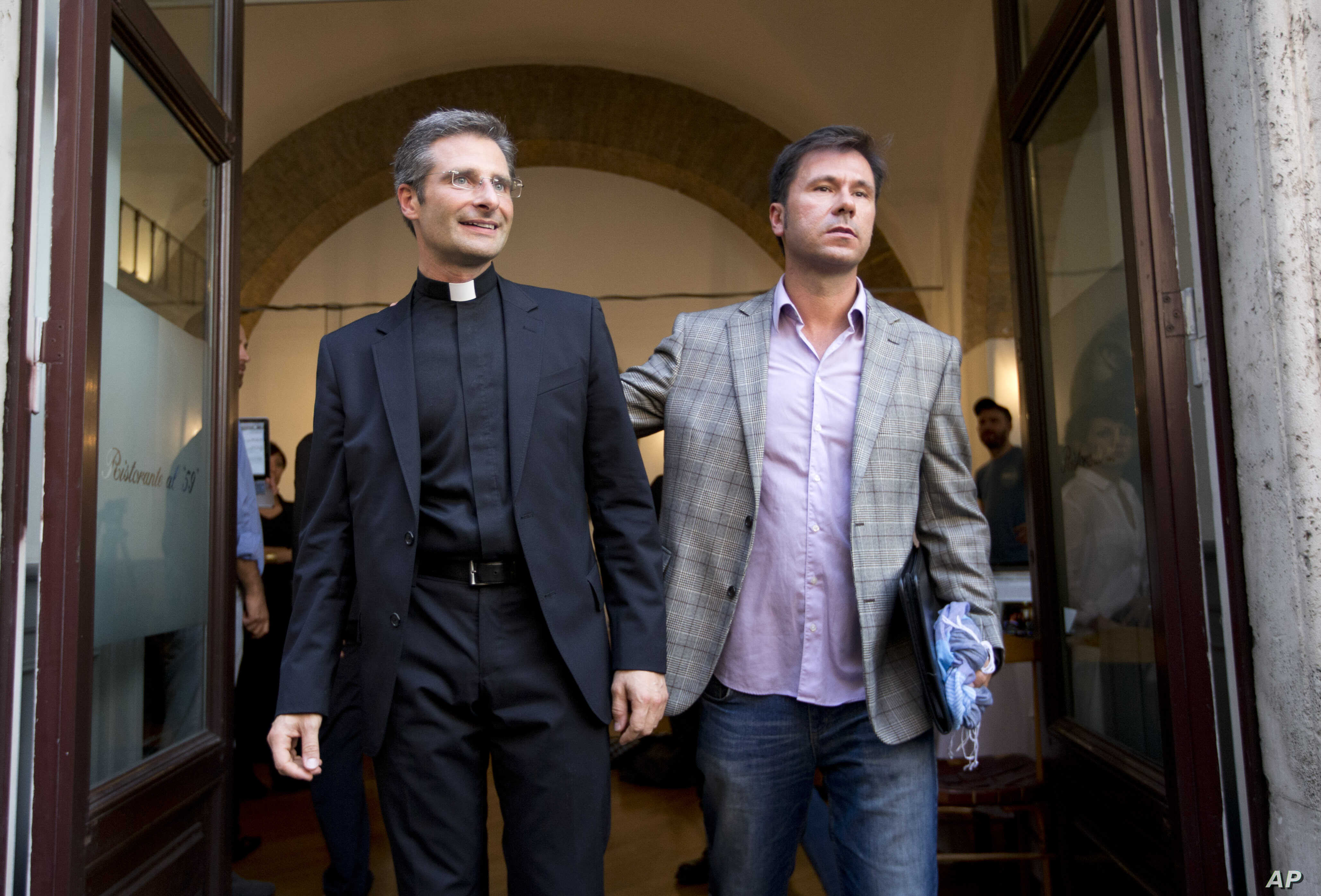 Monsignor Krzysztof Charamsa, left, and his boyfriend Eduard, surname not given, pose for a photo as they leave a restaurant after a news conference in downtown Rome, Oct. 3, 2015.