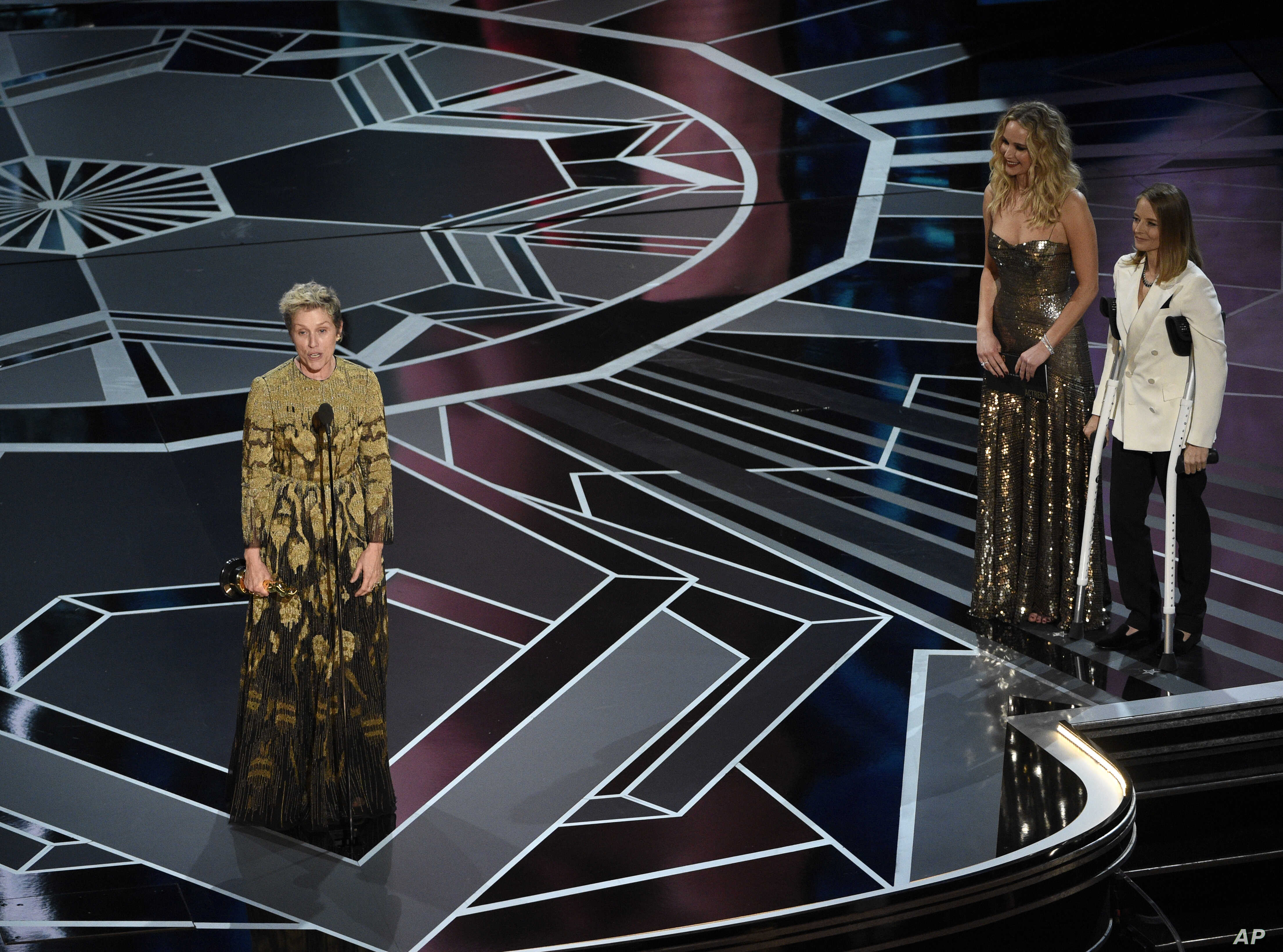 """Frances McDormand accepts the award for best performance by an actress in a leading role for """"Three Billboards Outside Ebbing, Missouri"""" as Jennifer Lawrence and Jodie Foster look on from right at the Oscars, March 4, 2018."""