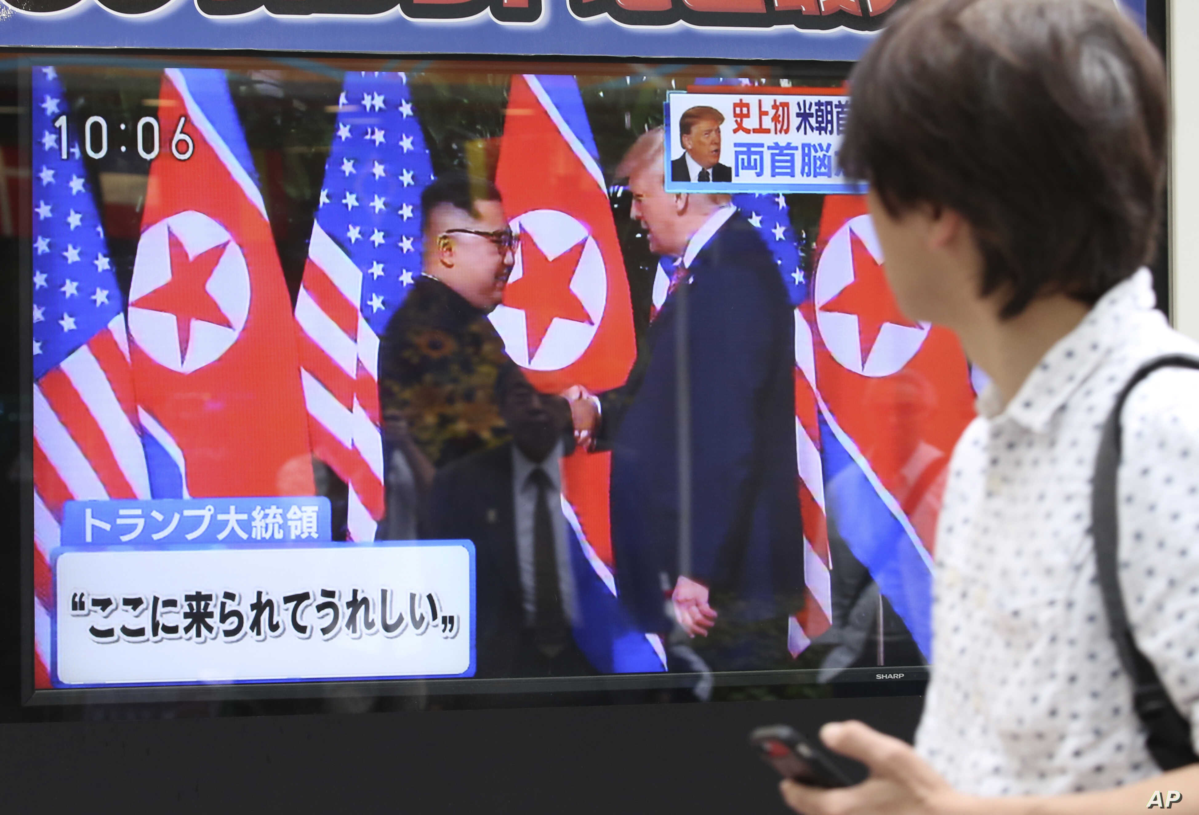 """A man looks at a TV screen showing North Korean leader Kim Jong Un, left, and U.S. President Donald Trump shaking hands before their meeting in Singapore, in Tokyo, June 12, 2018. Japanese letters read: """"Happy to come here."""""""