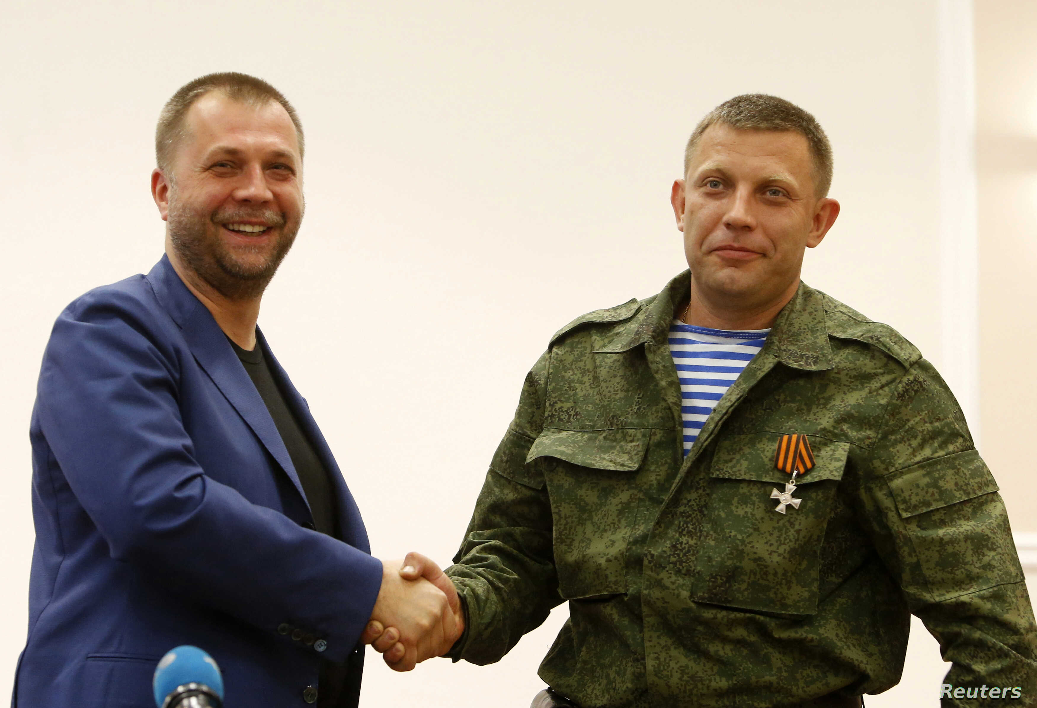 """Aleksander Borodai (L), leader of the self-proclaimed """"Donetsk People's Republic"""" shakes hands with rebel leader Aleksander Zakharchenko, during their news conference in Donetsk, August 7, 2014."""