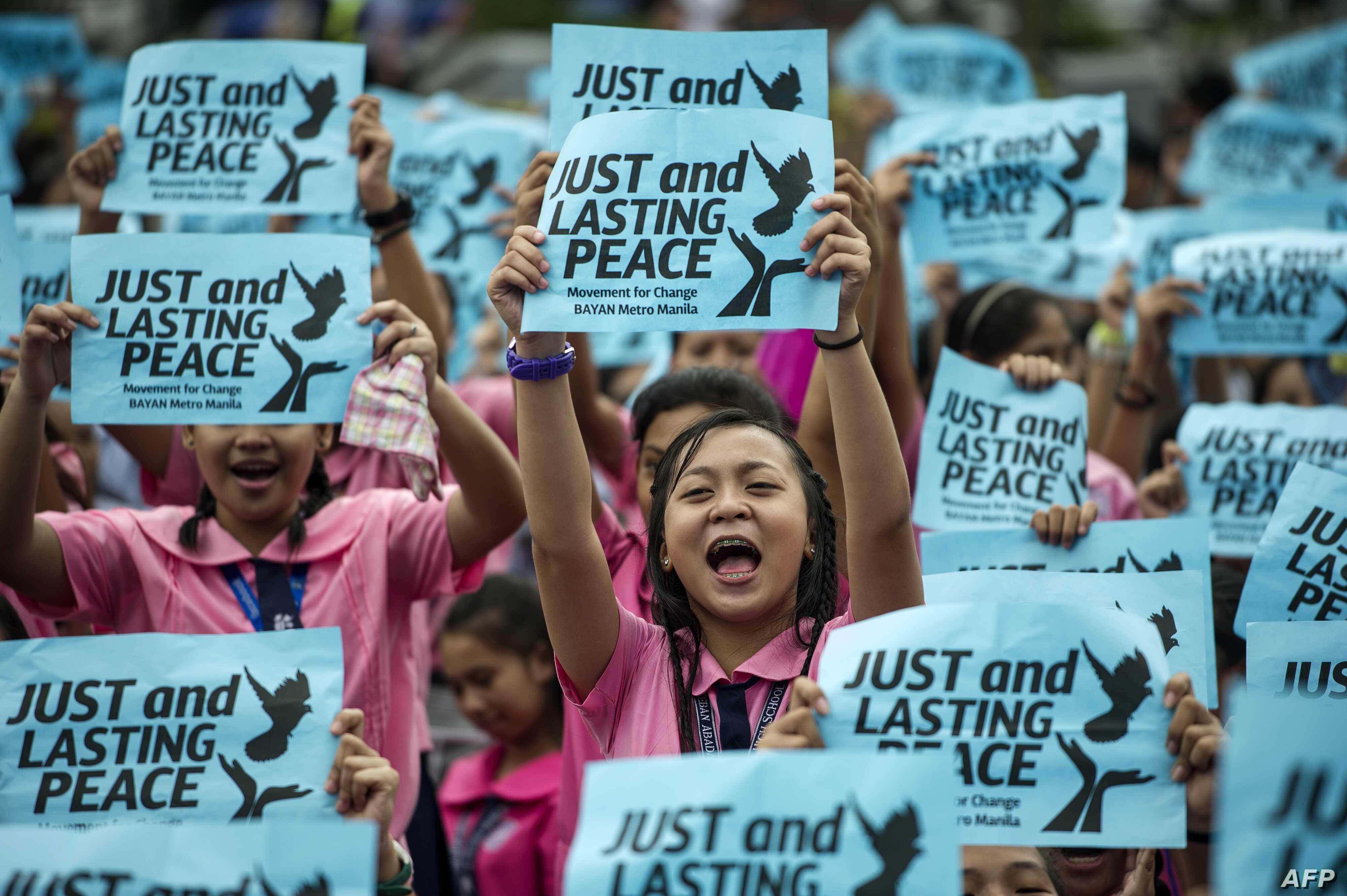 High school students hold banners calling for just and lasting peace as Philippine President Rodrigo Duterte marks his first 100 days in office in Manila, Oct. 7, 2016.
