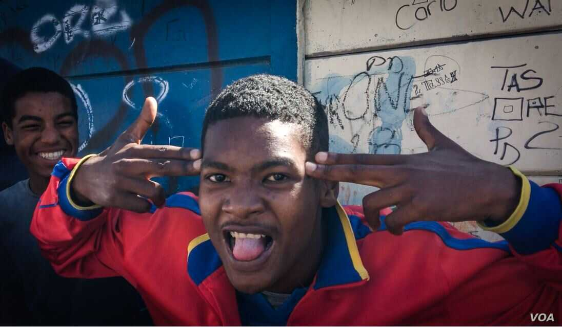 A young man postures, making a handgun gesture, in Cape Town's Hanover Park. Gang shootings are all too familiar in the township. (H. FitzPatrick/VOA)