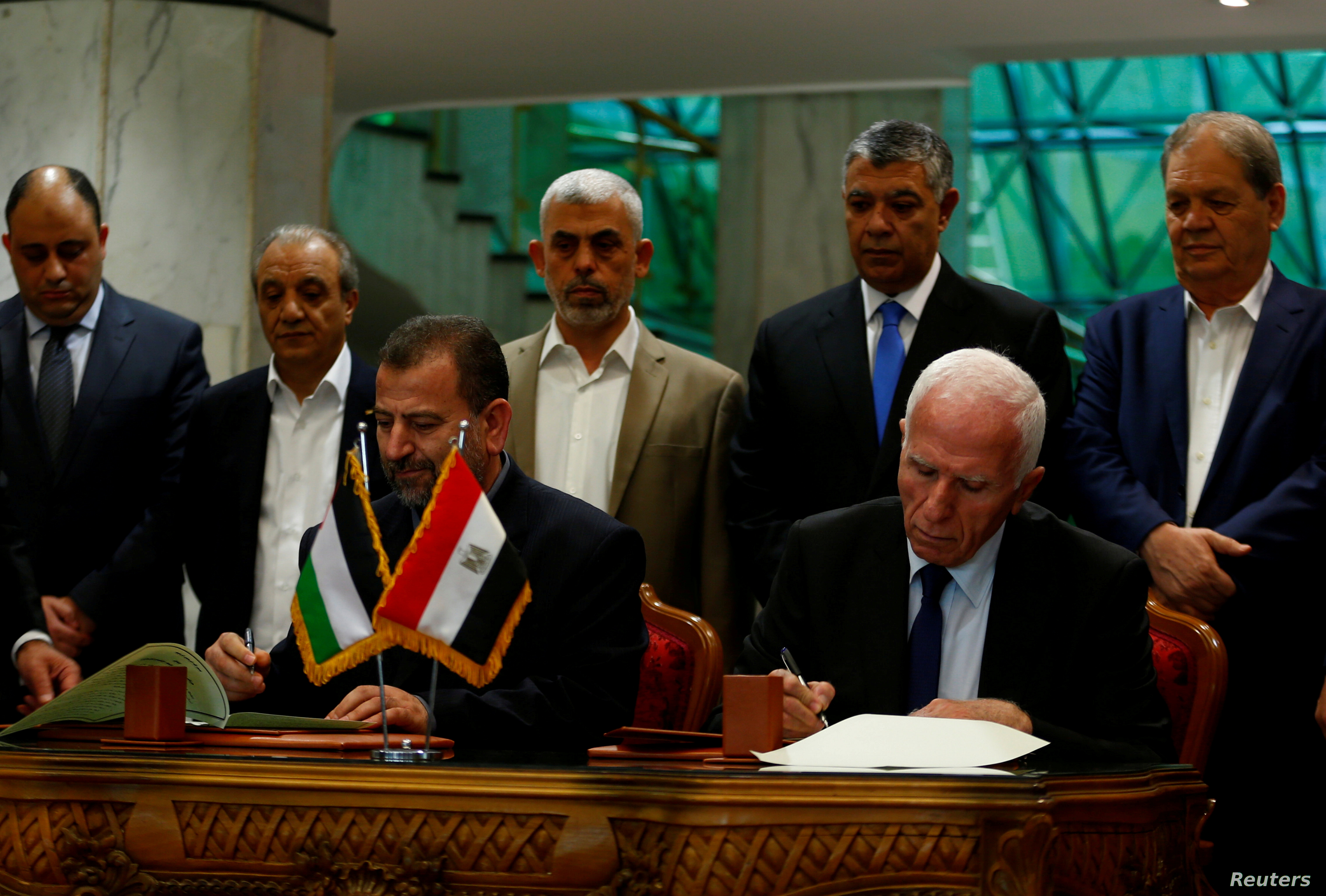 FILE PHOTO: Head of Hamas delegation Saleh Arouri and Fatah leader Azzam Ahmad sign a reconciliation deal in Cairo, Egypt, Oct. 12, 2017.