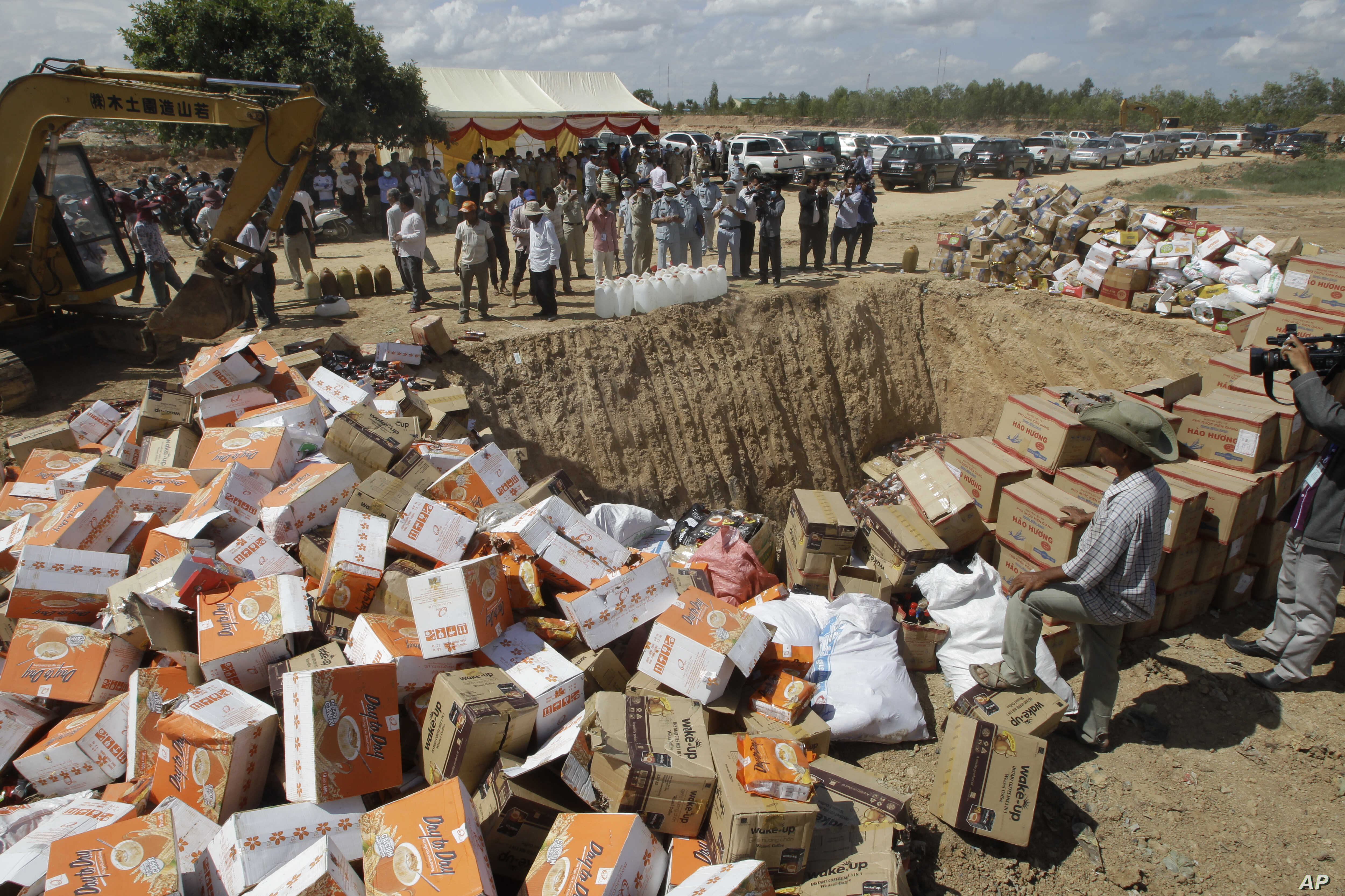 Cambodian police officers prepare to destroy counterfeit products at a dump site in Choeung Ek village on the outskirts of Phnom Penh, July 7, 2016.