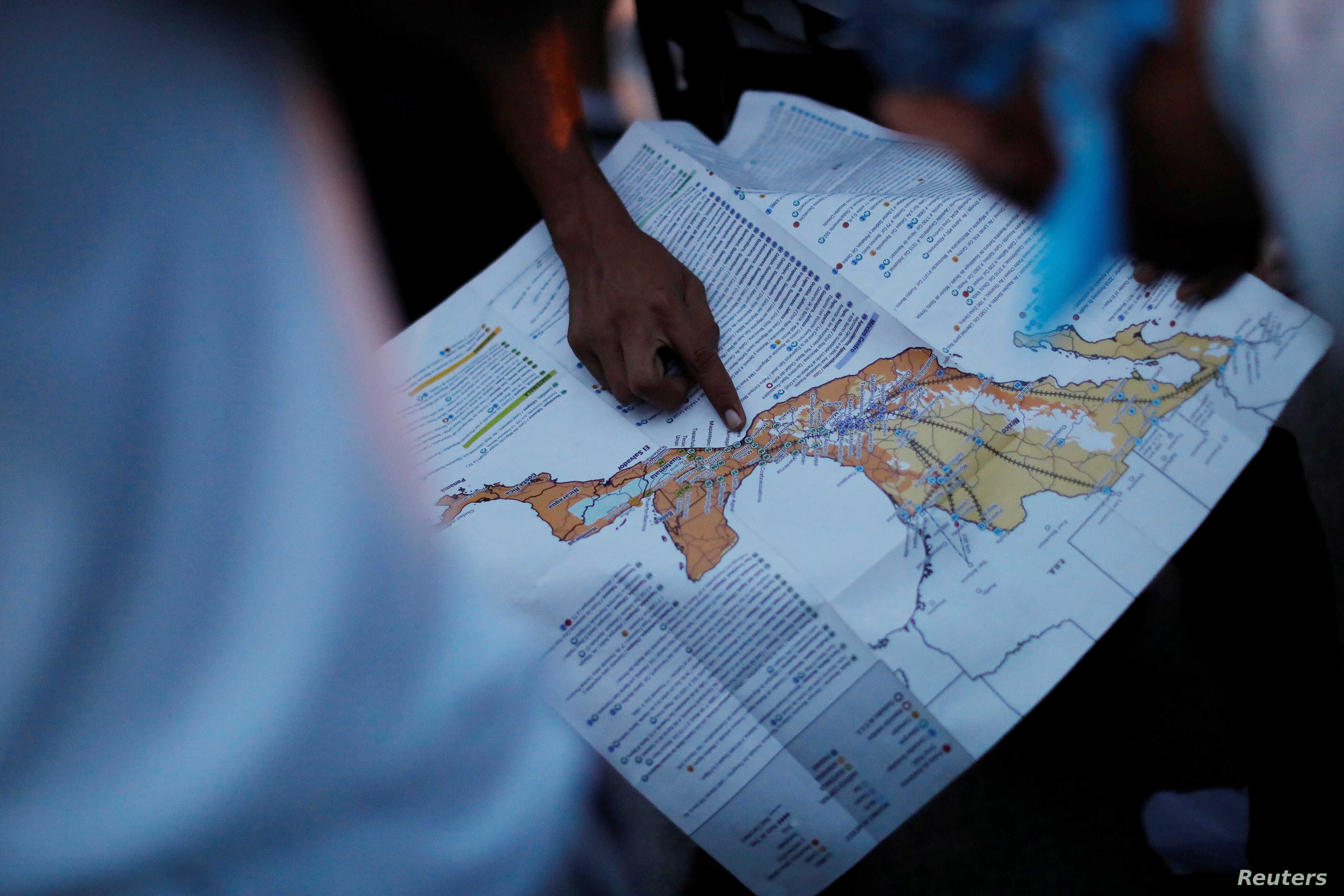 A migrant, part of a caravan of thousands traveling from Central America en route to the United States, points at a map while rest in Santiago Niltepec, Mexico, Oct. 29, 2018.