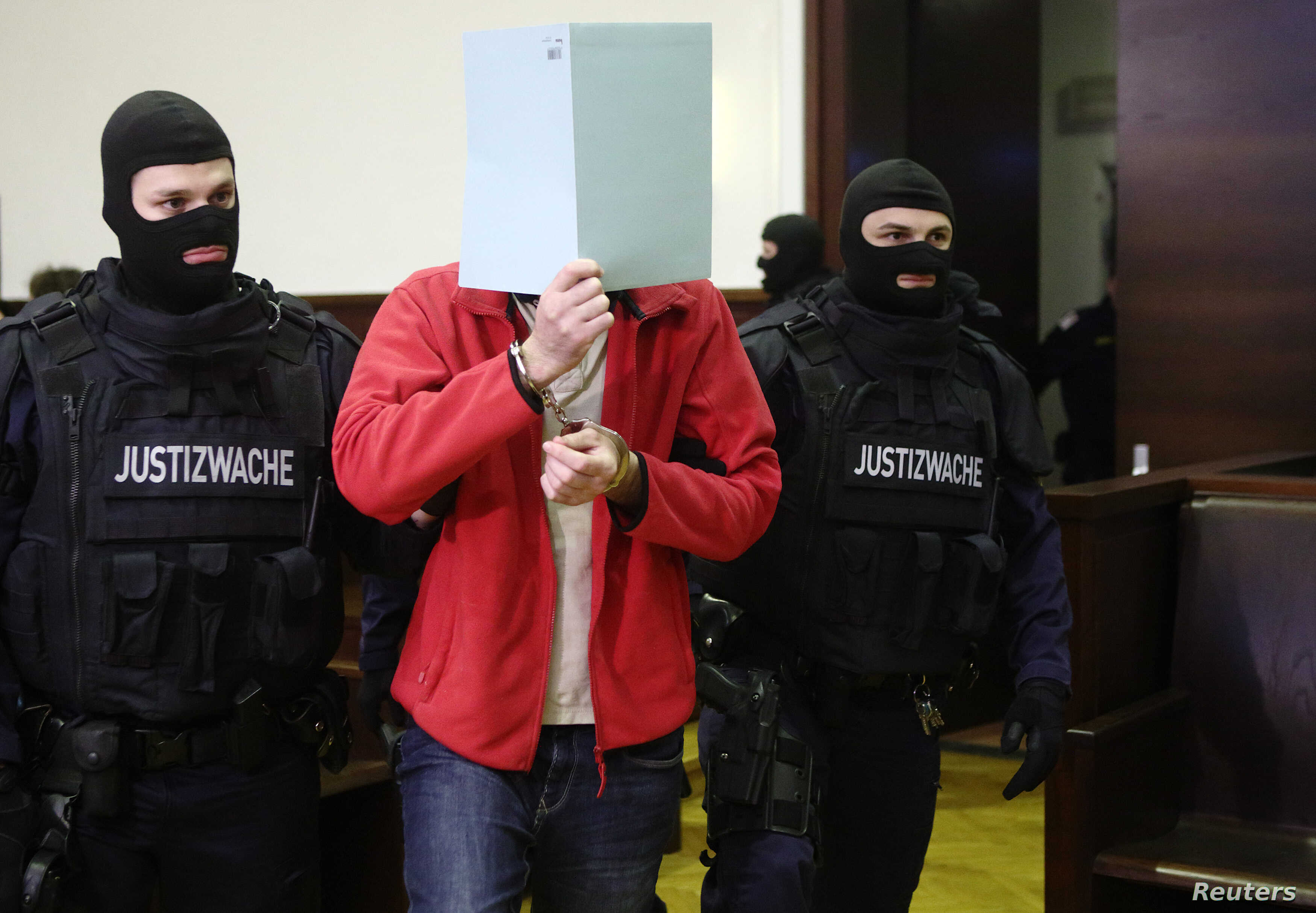 FILE - Defendant Magomed Z., a 30-year-old ethnic Chechen, is led into court for the start of his trial in Krems, Austria, Jan. 22. Austrian authorities accused him of fighting with IS militants in Syria in 2013.