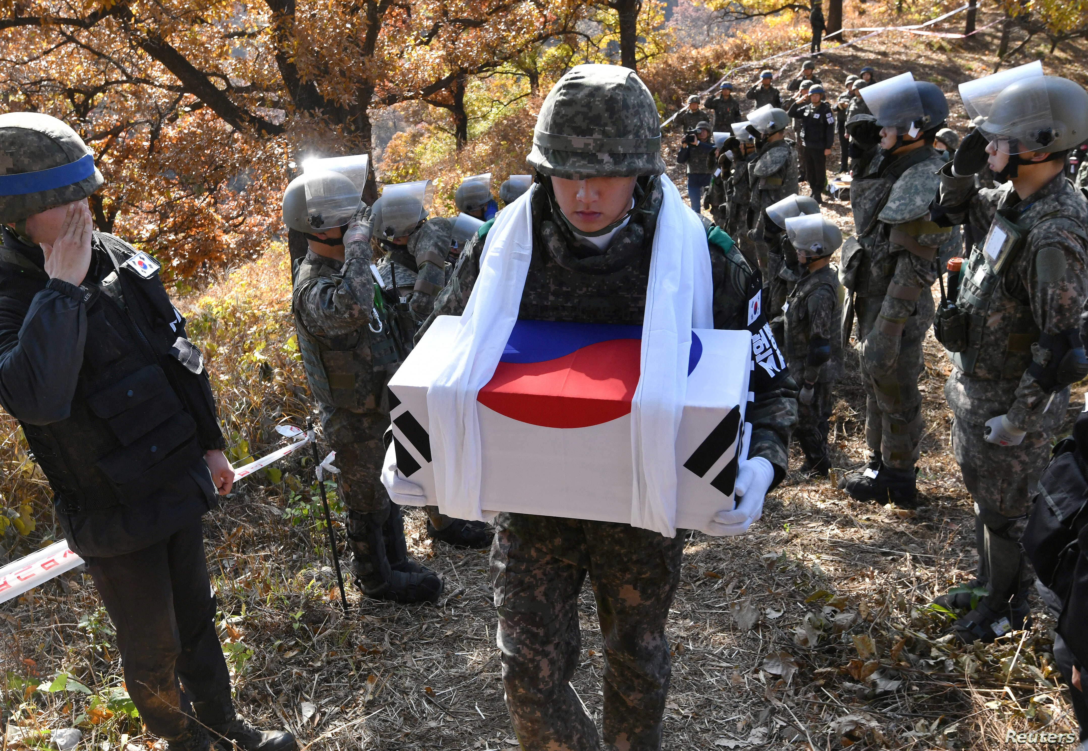 A South Korean soldier carries a casket containing a piece of bone believed to be the remains of an unidentified South Korean soldier killed in the Korean War in the Demilitarized Zone (DMZ) dividing the two Koreas in Cheorwon, South Korea October 25...