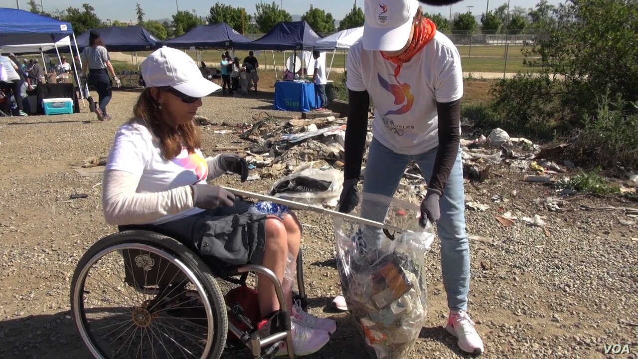 """Candice Cable helps pick up trash from the Los Angles River, April 15, 2017. Cable, a member of the committee to bring the Olympic Games to Los Angeles, says the volunteer-run program to bring the Summer Games to the city in 2024 hopes to """"get futu..."""