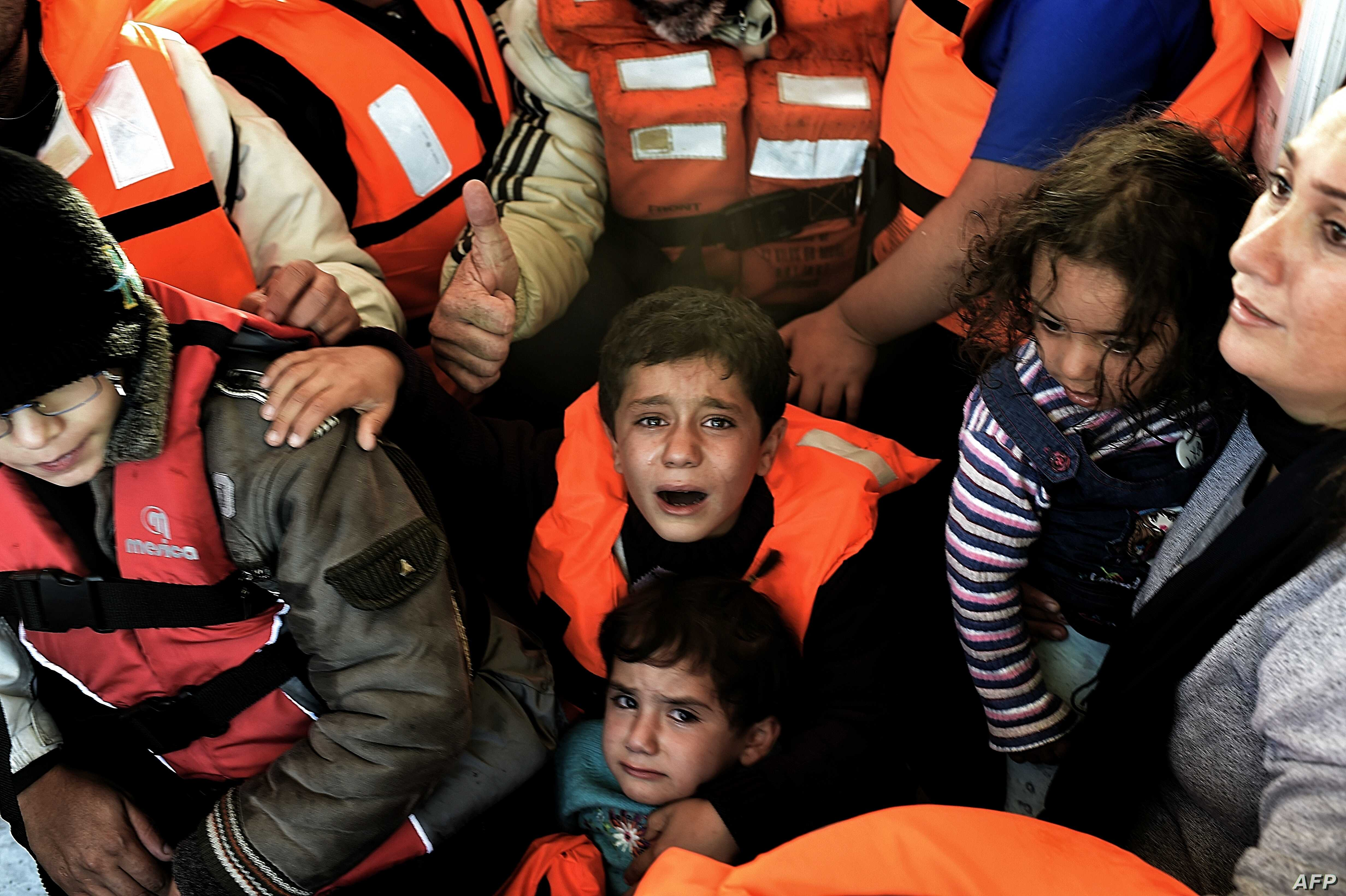 Syrian Kurdish refugees are rescued by Greek fishermen as the boat they were on sinks off the Greek island of Lesbos after crossing the Aegean Sea from Turkey, Oct. 30, 2015.