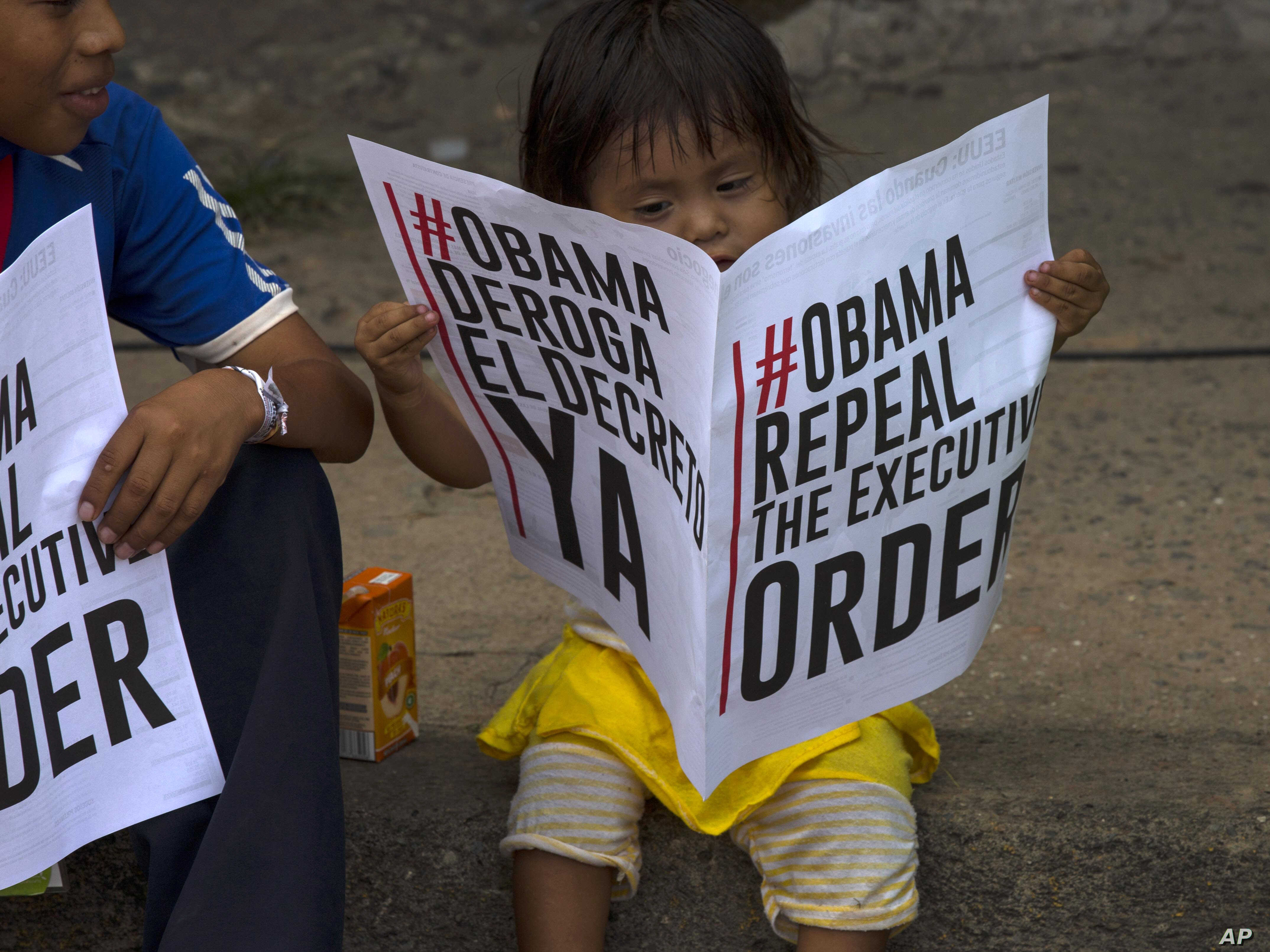 A child looks at a bilingual leaflet in favor of the U.S. repealing sanctions against Venezuela.