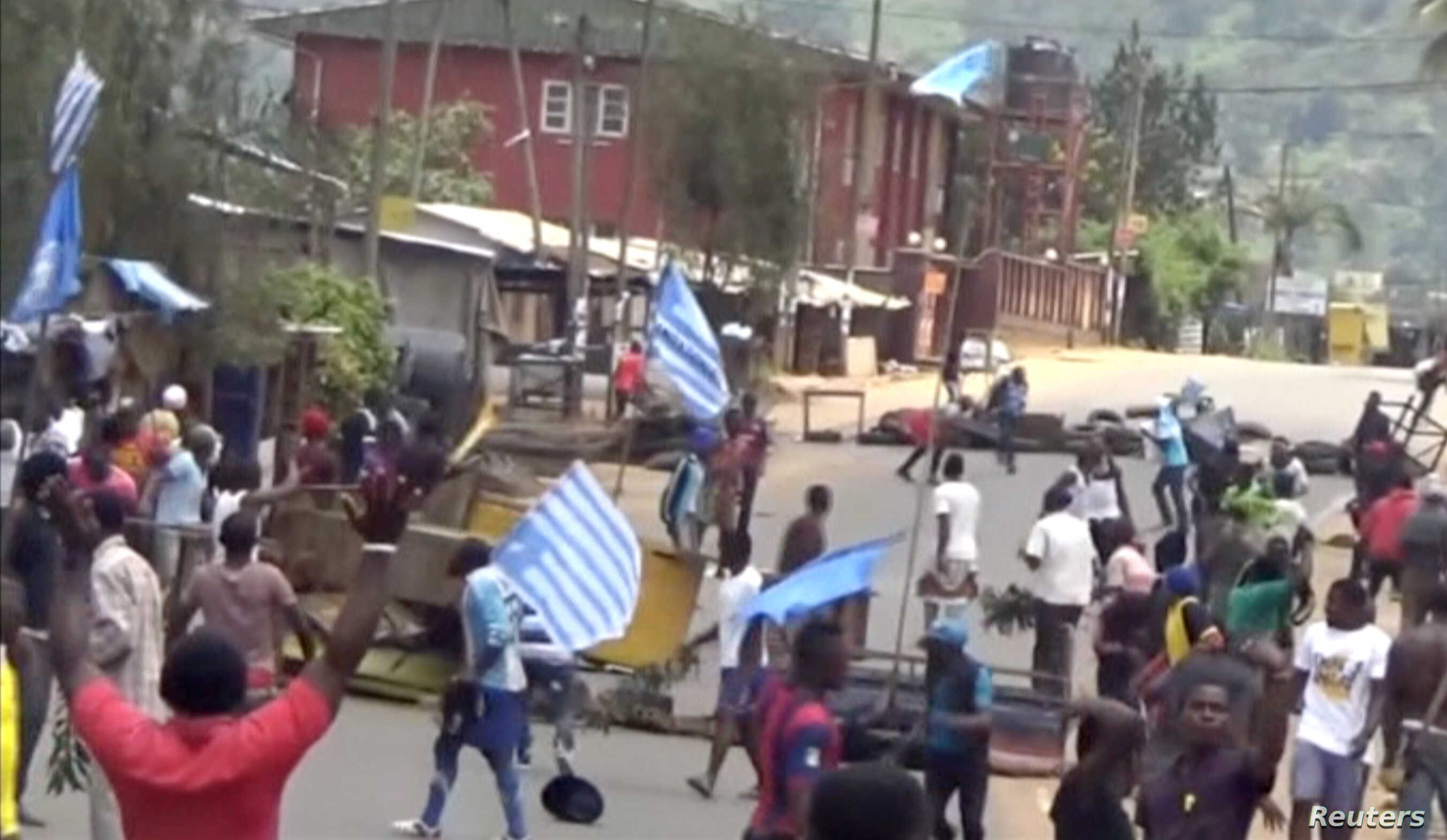 A still image taken from a video shot on Oct. 1, 2017, shows protesters waving Ambazonian flags in front of road block in the English-speaking city of Bamenda, Cameroon.