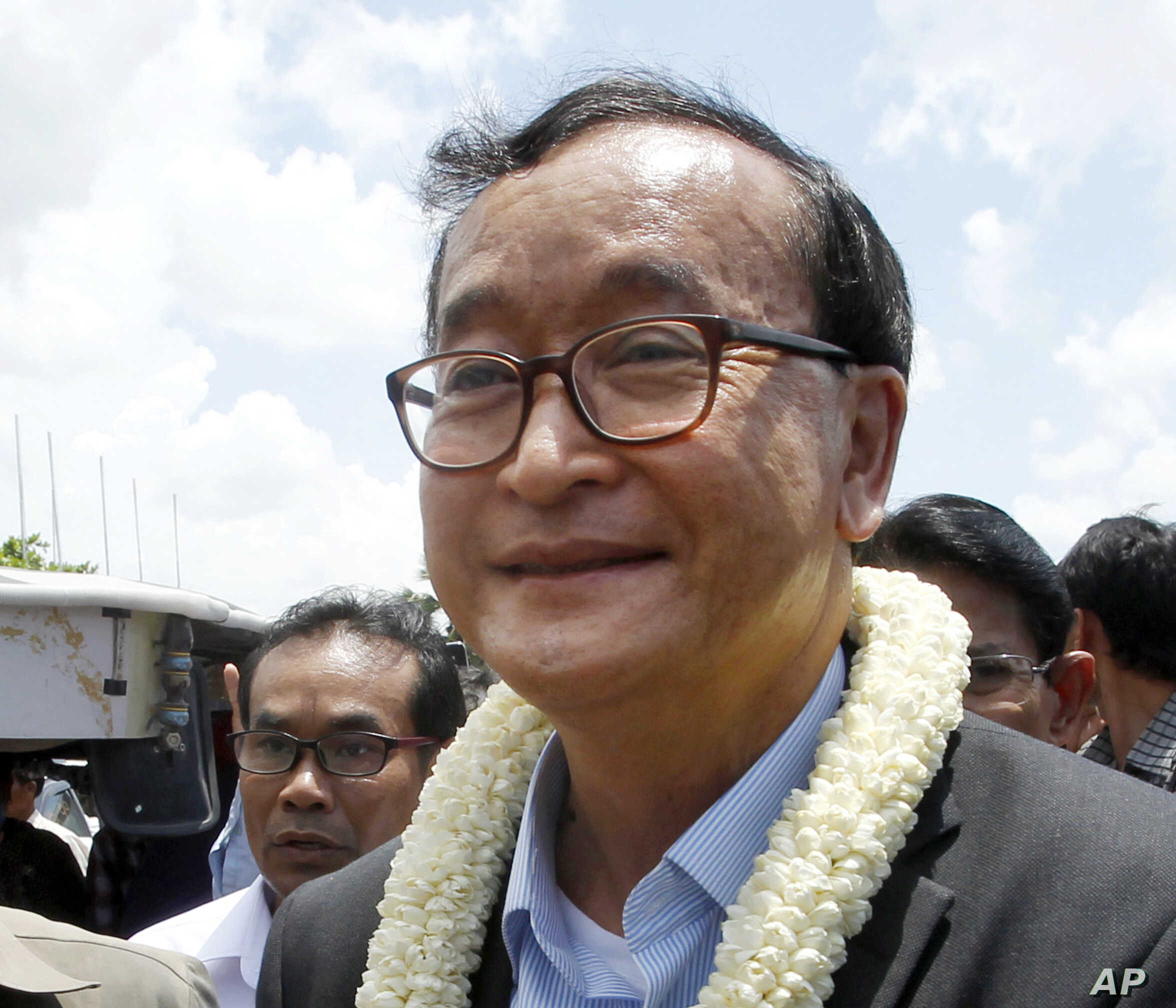 FILE - In this Aug. 16, 2015, file photo, Sam Rainsy, leader of the opposition Cambodia National Rescue Party, greets his party supporters upon his arrival at Phnom Penh International Airport in Phnom Penh, Cambodia. The Phnom Penh Municipal Court on...
