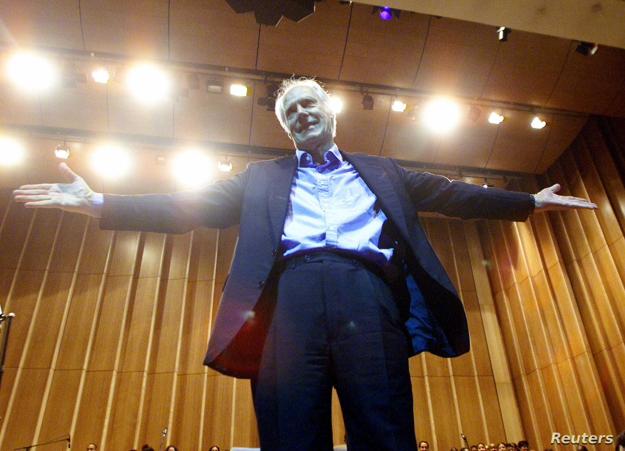 """FILE - Legendary producer of """"The Beatles"""", Sir George Martin, gestures after conducting the Cuban National Symphony Orchestra, November 1, 2002."""