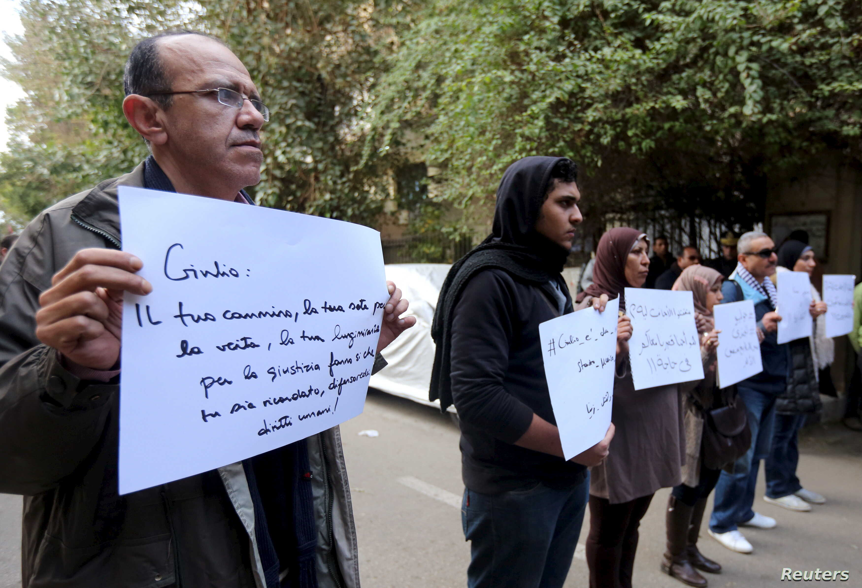 """Activists hold placards that read, among others, """"Giulio, one of us and killed like us,"""" during a memorial for Giulio Regeni outside of the Italian embassy in Cairo, Egypt, Feb. 6, 2016."""
