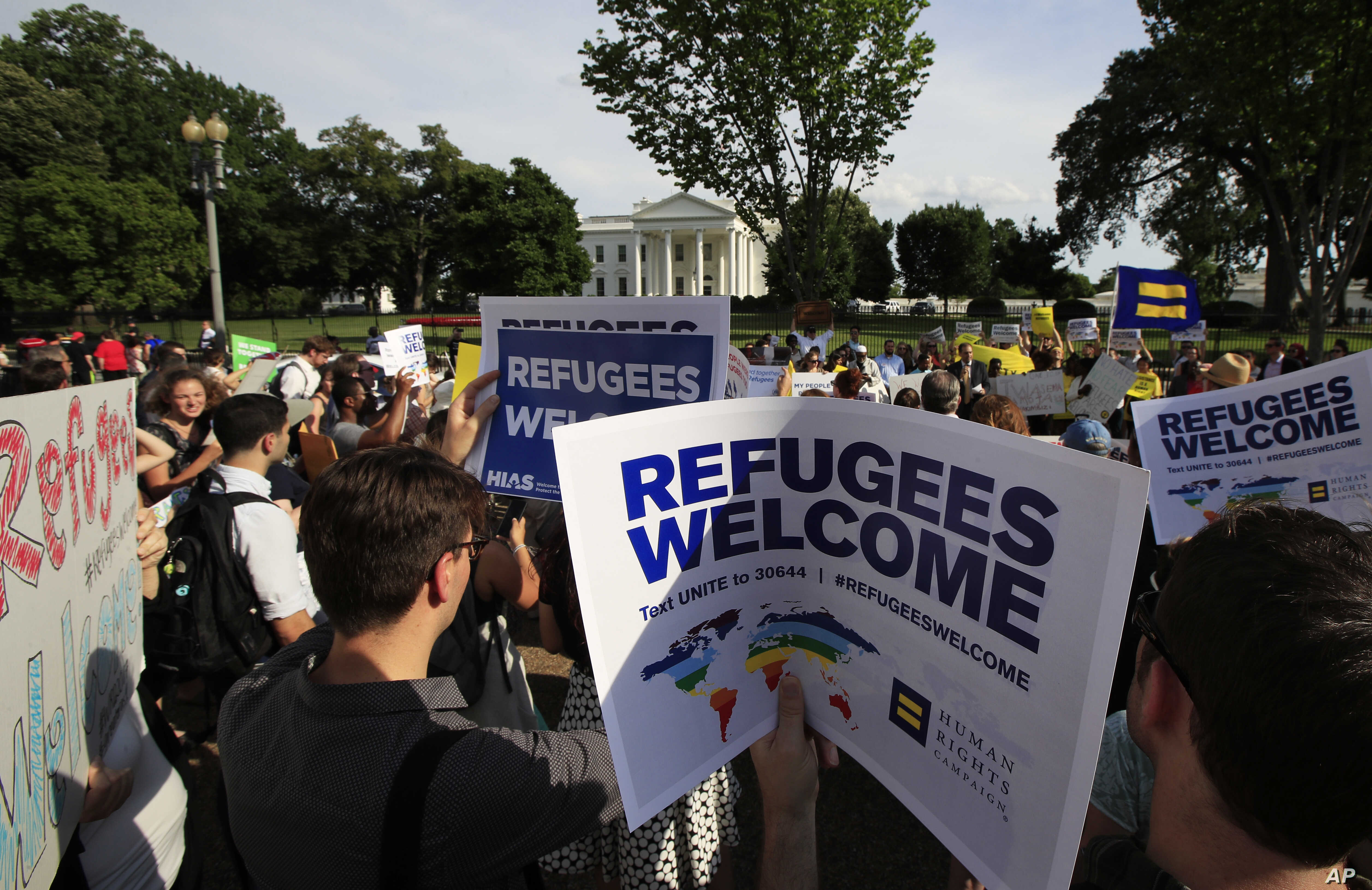FILE - Refugees and community activists gather in front of the White House in Washington, June 20, 2017, during a rally in solidarity with refugees to commemorate World Refugee Day.