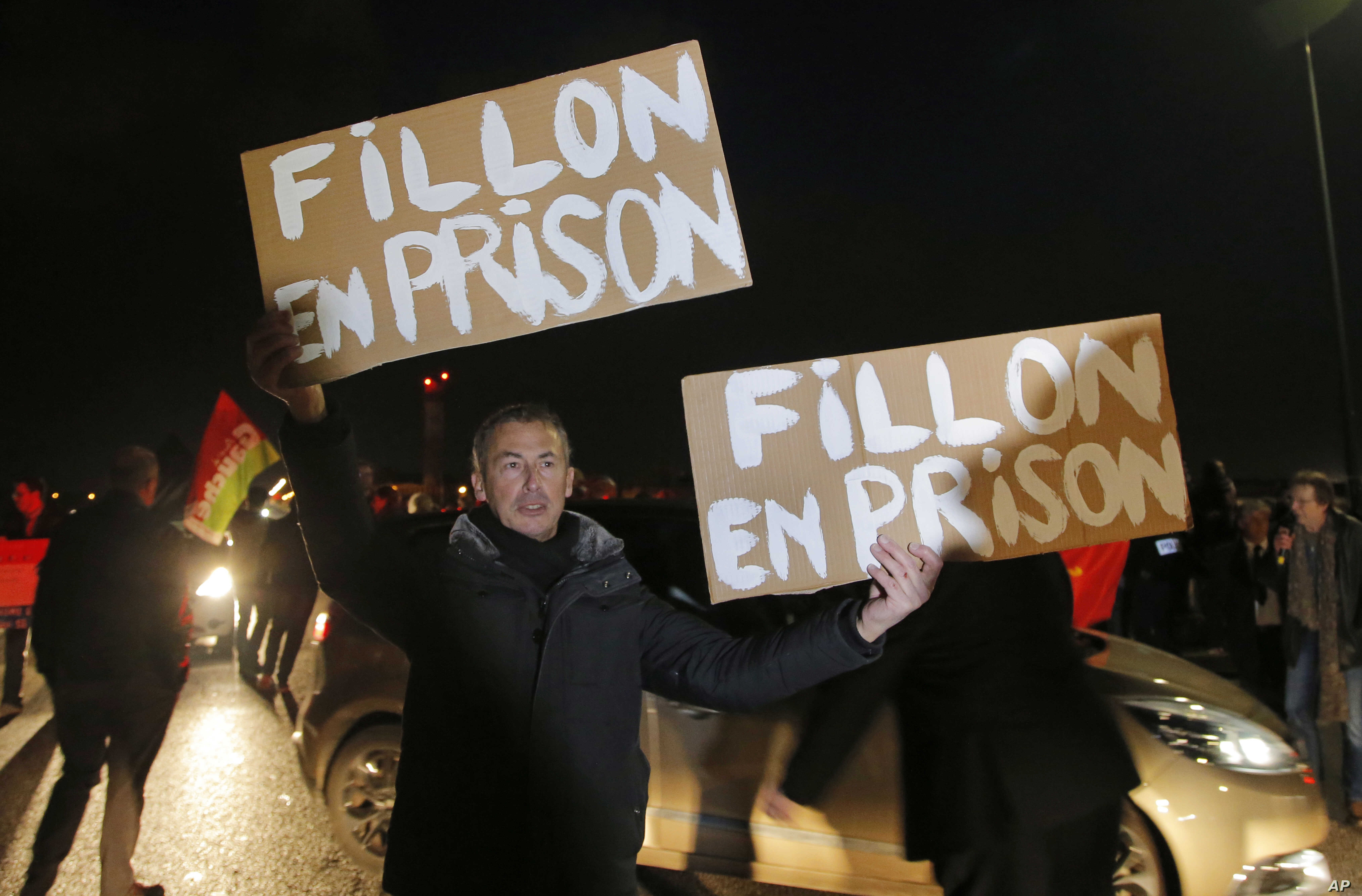"""A demonstrator holds placards reading """"Fillon in jail' ahead of the French conservative presidential candidate Francois Fillon's campaign rally in Compiegne, north of Paris, Feb. 15, 2017."""