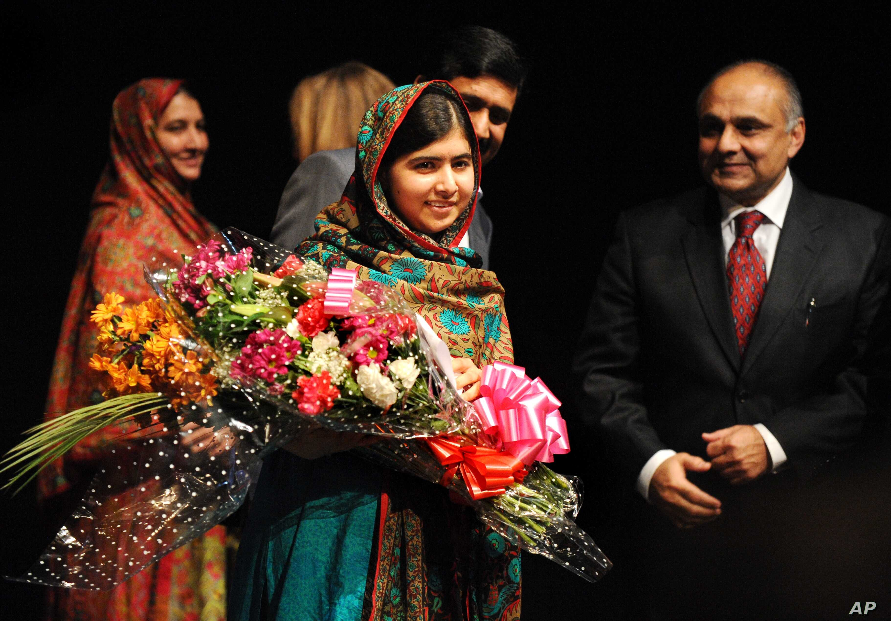 Malala Yousafzai holds flowers after speaking during a media conference at the Library of Birmingham, in Birmingham, England, Oct. 10, 2014, after she was named as winner of The Nobel Peace Prize.