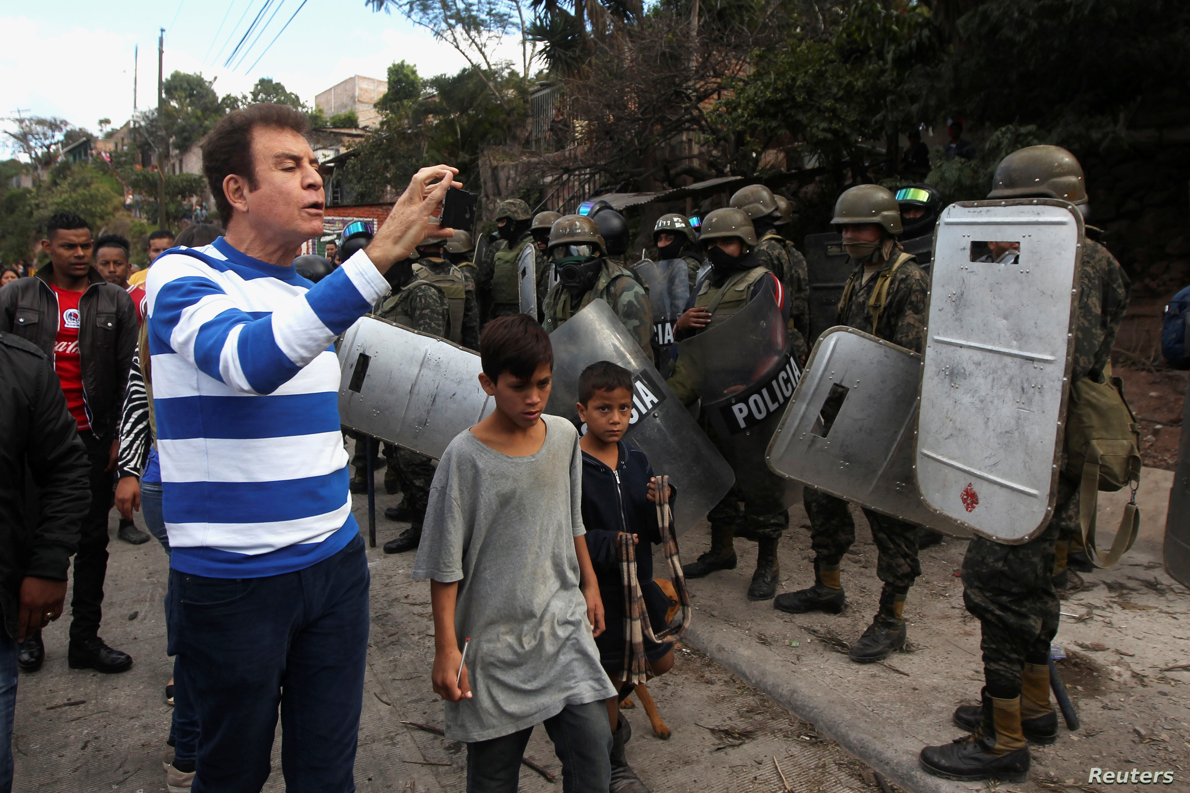 Opposition candidate Salvador Nasralla takes video of soldiers during a protest against the re-election of Honduran President Juan Orlando Hernandez in Tegucigalpa, Honduras, Jan. 20, 2018.