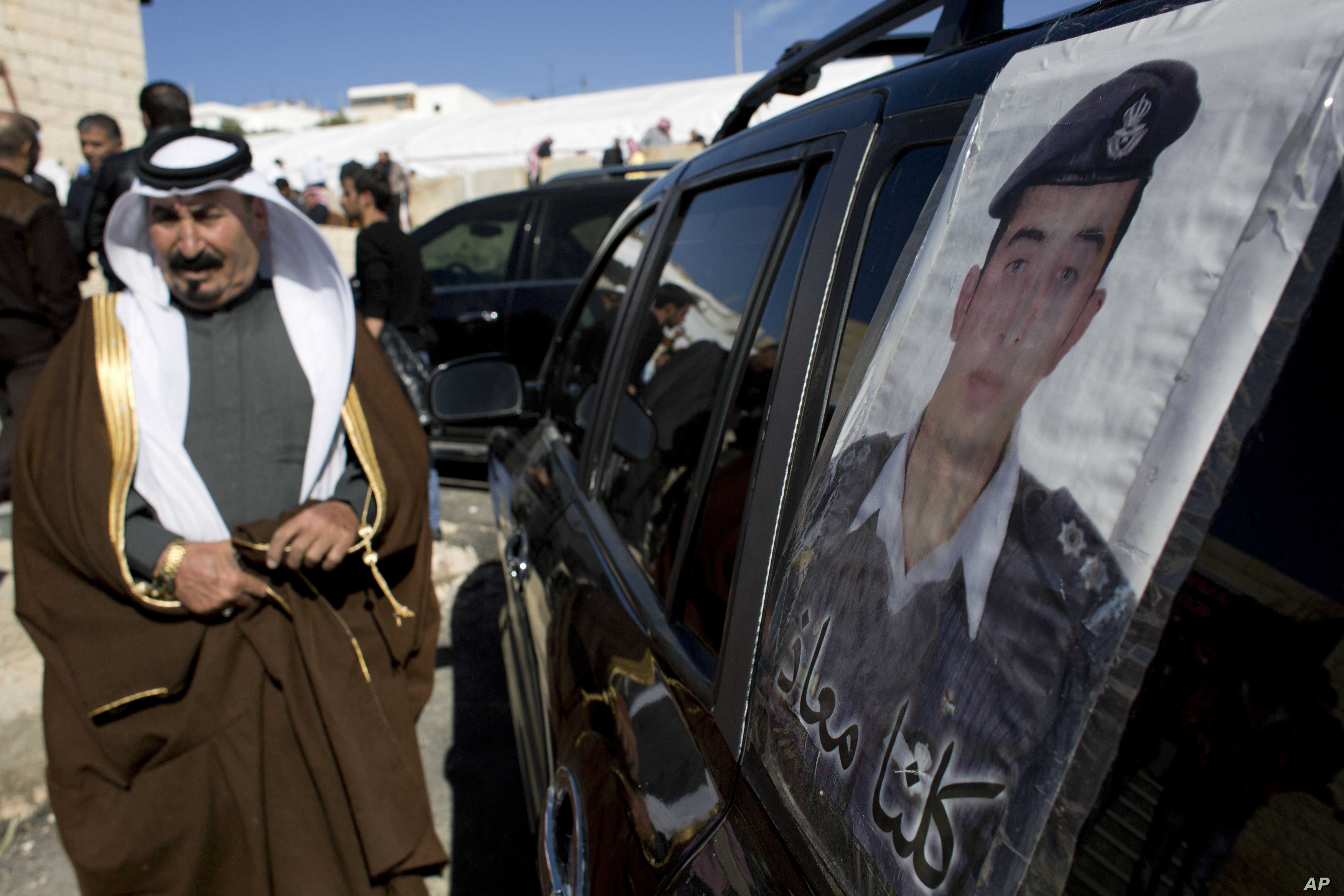 """A Jordanian man walks past a poster that is pasted on a vehicle with a picture of slain Jordanian pilot, Lt. Muath al-Kaseasbeh with Arabic that reads, """"we are all Muath,"""" at his home village of Ai, near Karak, Jordan, Feb. 4, 2015."""