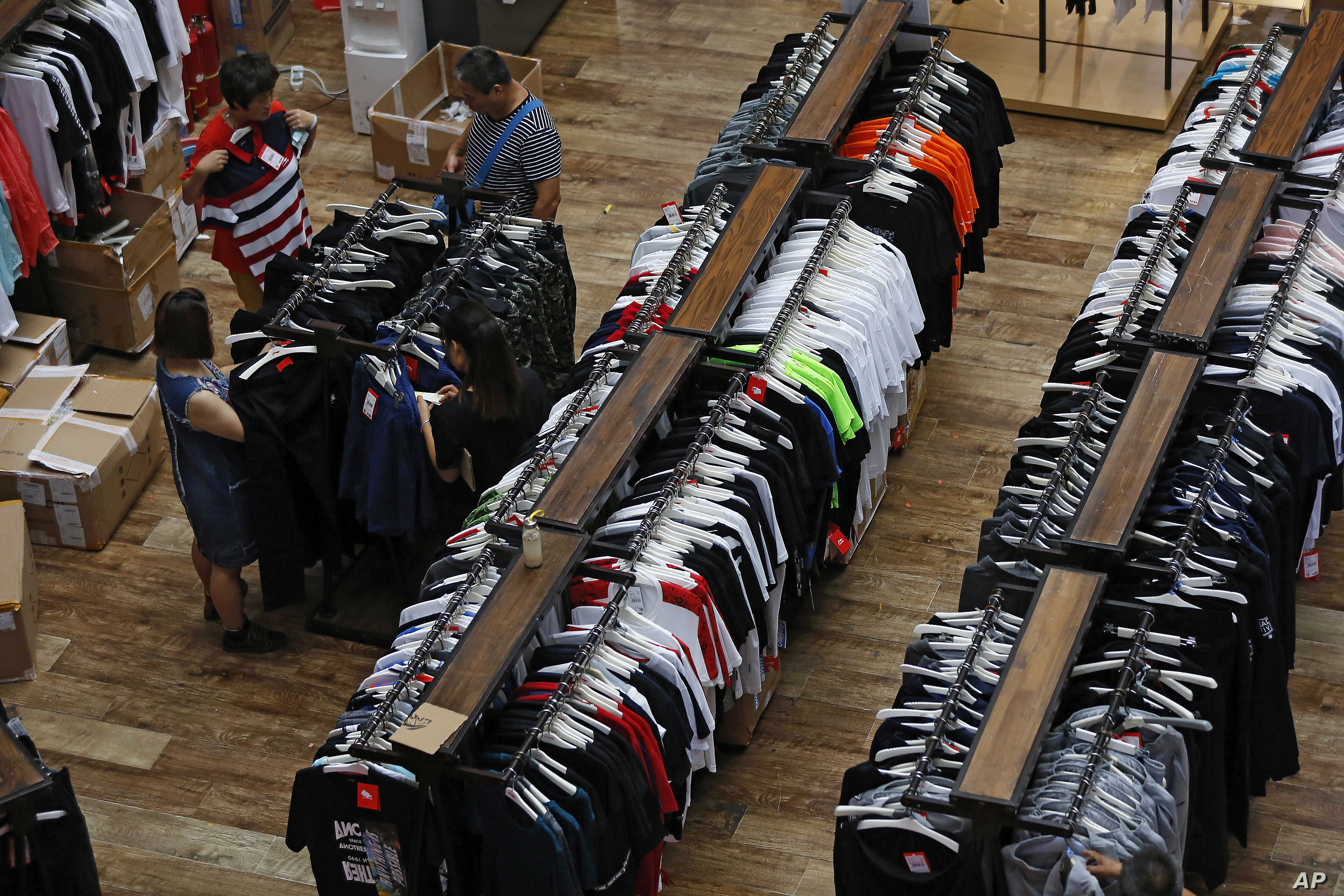 People try garments at a retail and wholesale clothing mall in Beijing, July 16, 2018. China's economic growth slowed in the quarter ending in June, adding to challenges for Beijing amid a mounting tariff battle with Washington.
