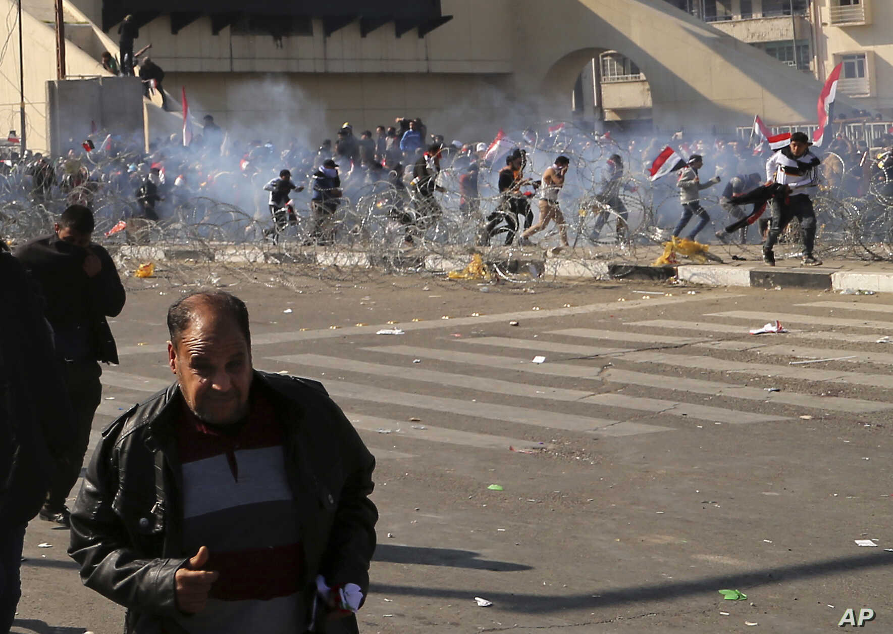 Protesters run from tear gas fired by security forces, during a demonstration by followers of Iraq's influential Shi'ite cleric Muqtada al-Sadr, in Baghdad, Iraq, Feb. 11, 2017.