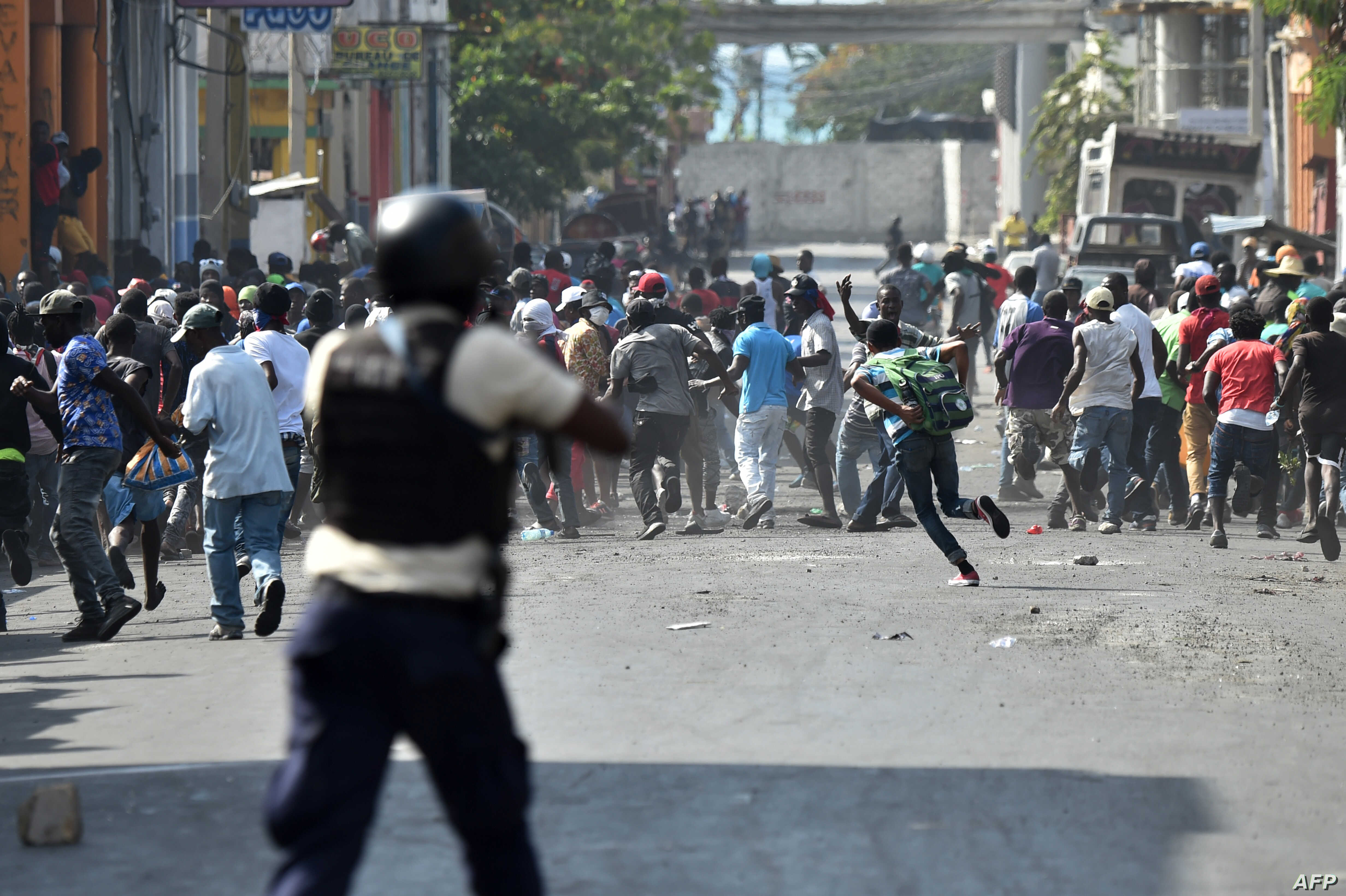 Demonstrators flee as Haitian police open fire during clashes in the center of the Haitian capital of Port-au-Prince, Feb. 13, 2019.