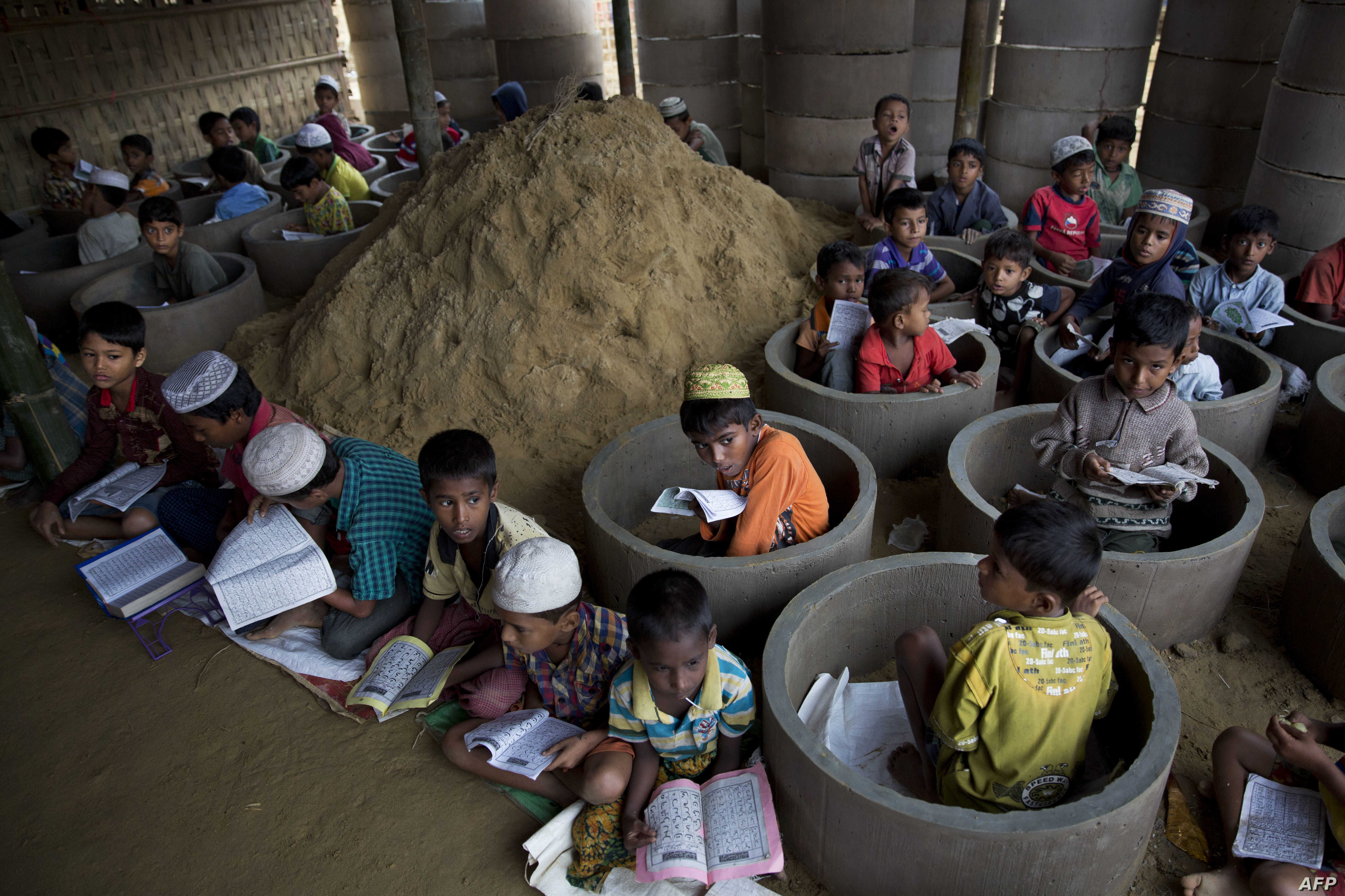 Rohingya refugee children attend recitation classes of the holy Quran in a newly opened madrasa, or religious school, amid material stocked for constructing latrines in Balukhali refugee camp, Bangladesh, Monday, Oct. 30, 2017.