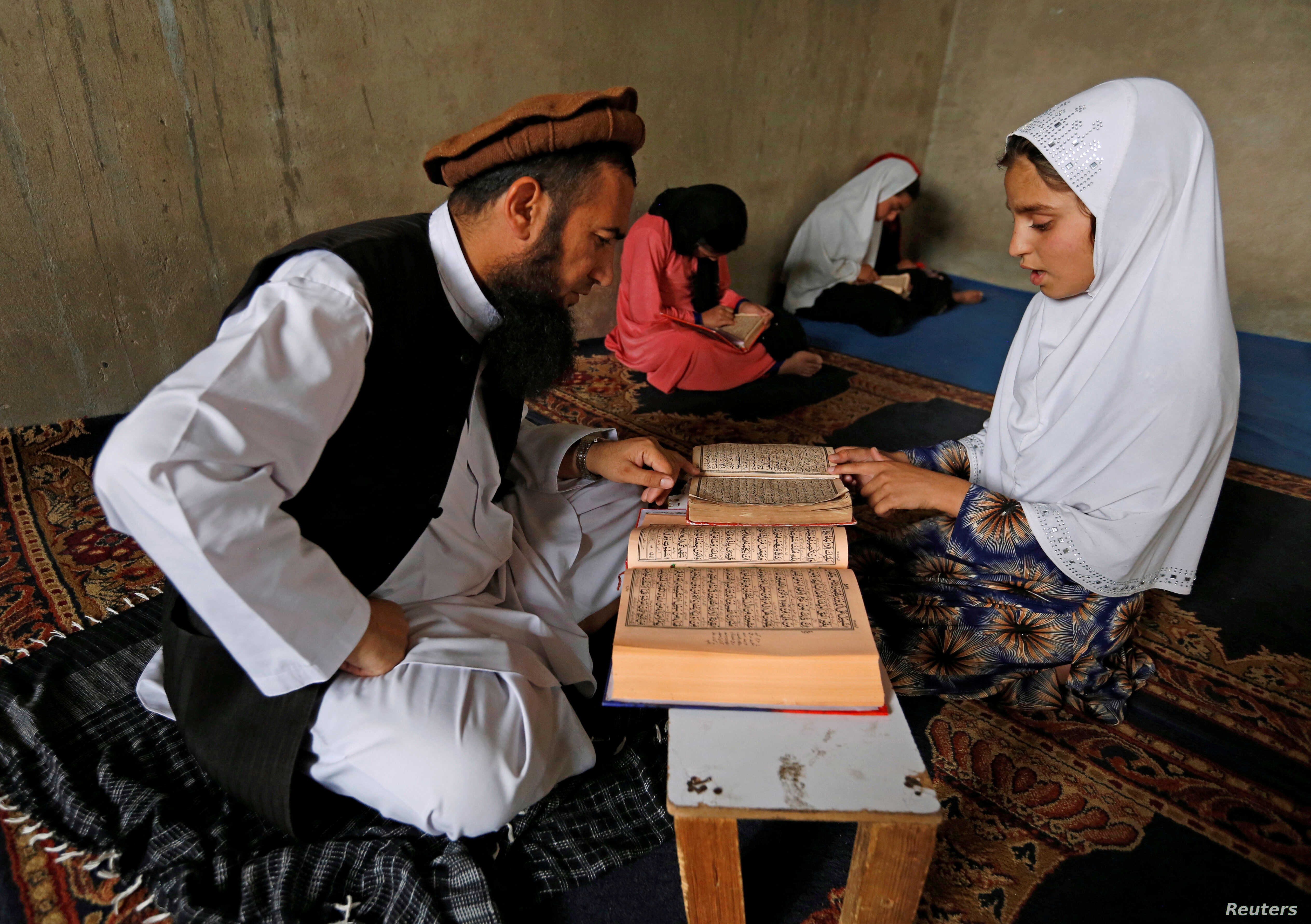 An Afghan girl reads the Koran in a madrasa, a religious school, during the holy month of Ramadan in Kabul, Afghanistan June 16, 2016.