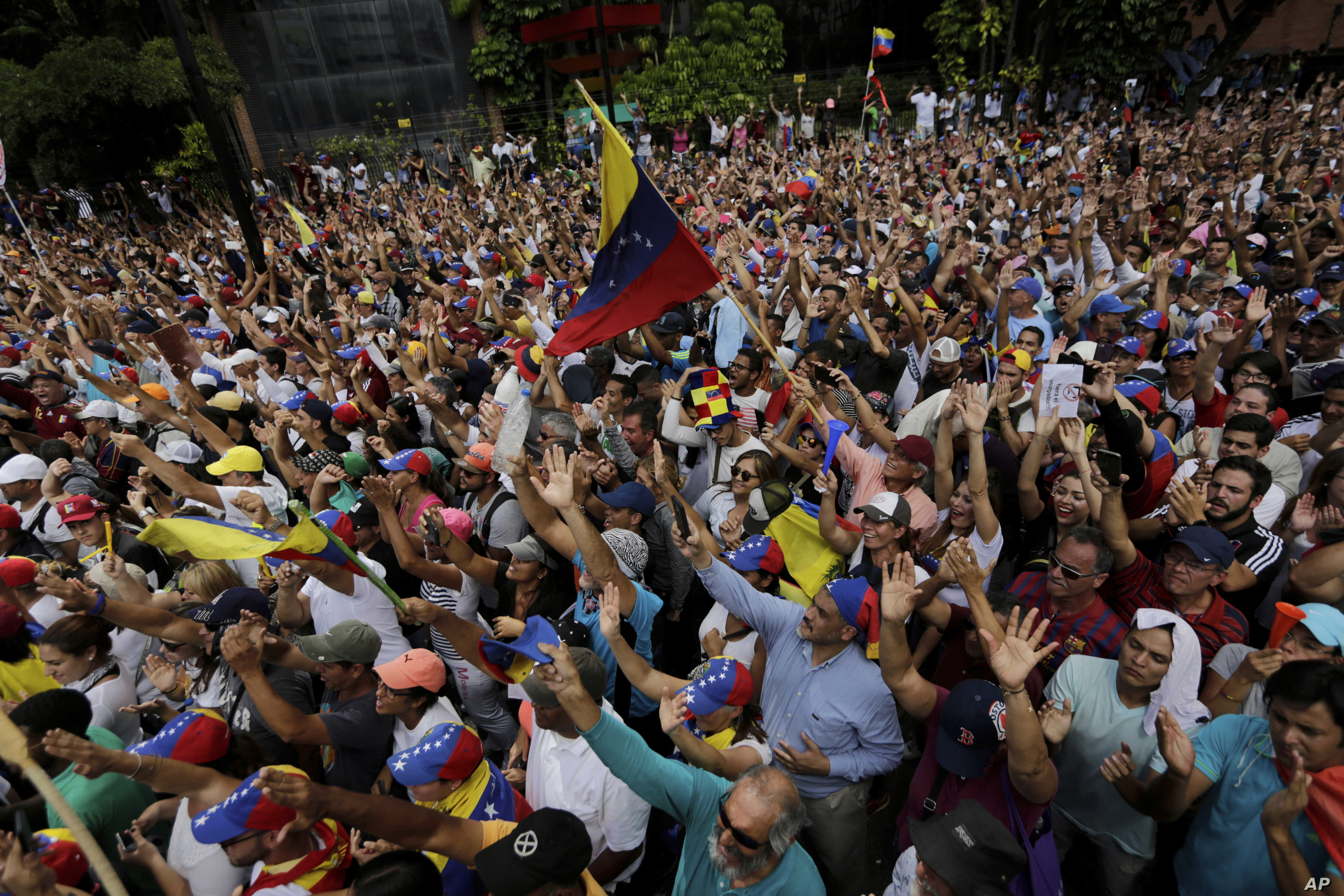 Anti-government protesters hold their hands up during the symbolic swearing-in of Juan Guaido, head of the opposition-run congress who declared himself interim president of Venezuela until elections can be called, during a rally demanding President N...