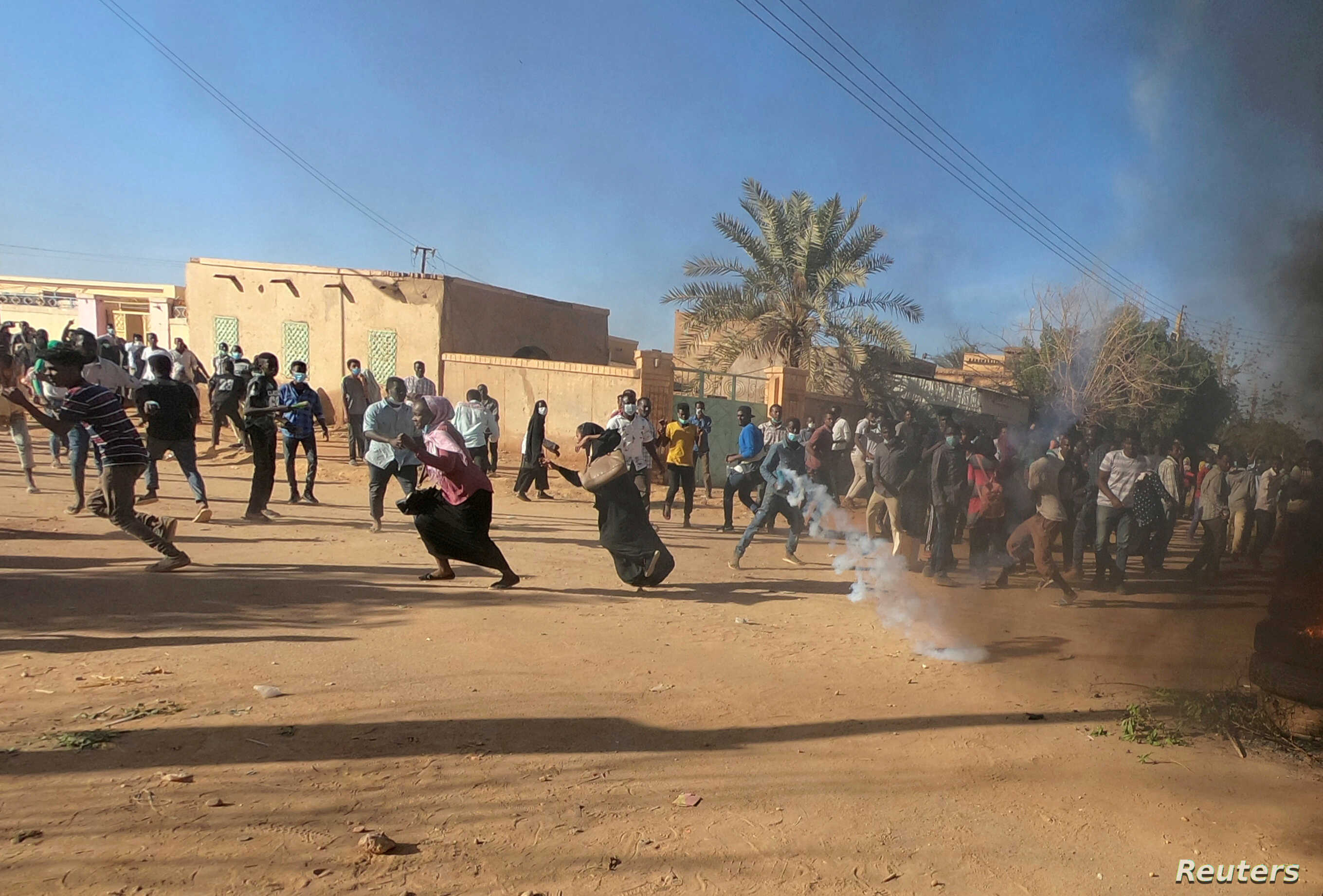 FILE - Sudanese demonstrators run from a teargas canister fired by riot policemen to disperse them as they participate in anti-government protests in Omdurman and Khartoum, Sudan, Jan. 20, 2019.
