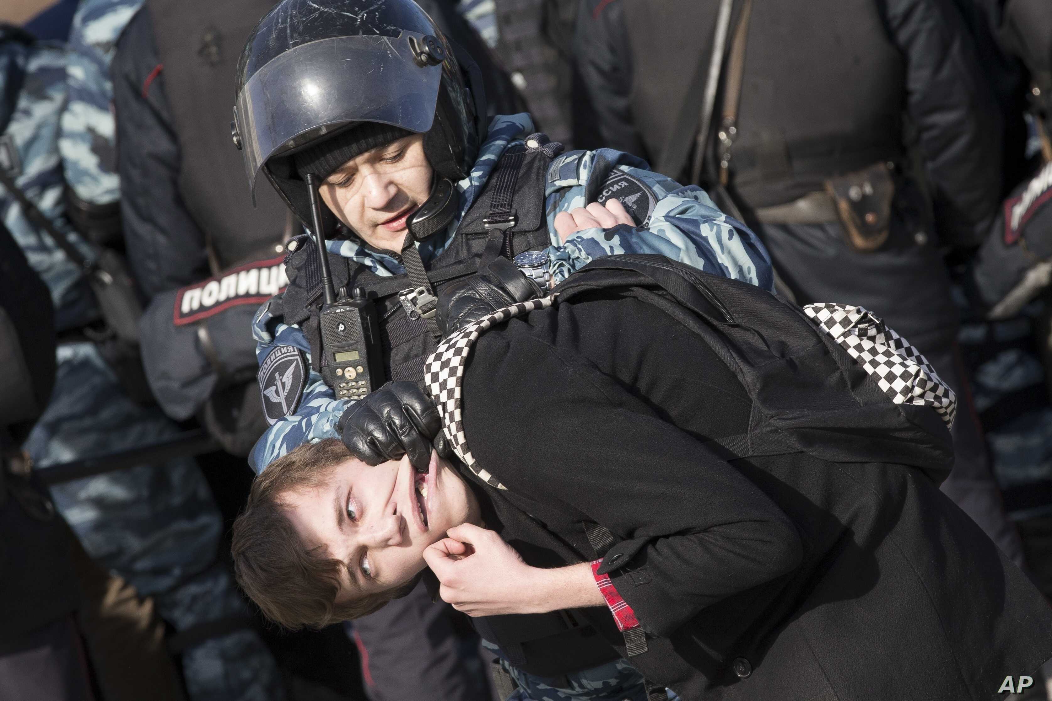 Police detain a protester in downtown Moscow, Russia, Sunday, March 26, 2017.