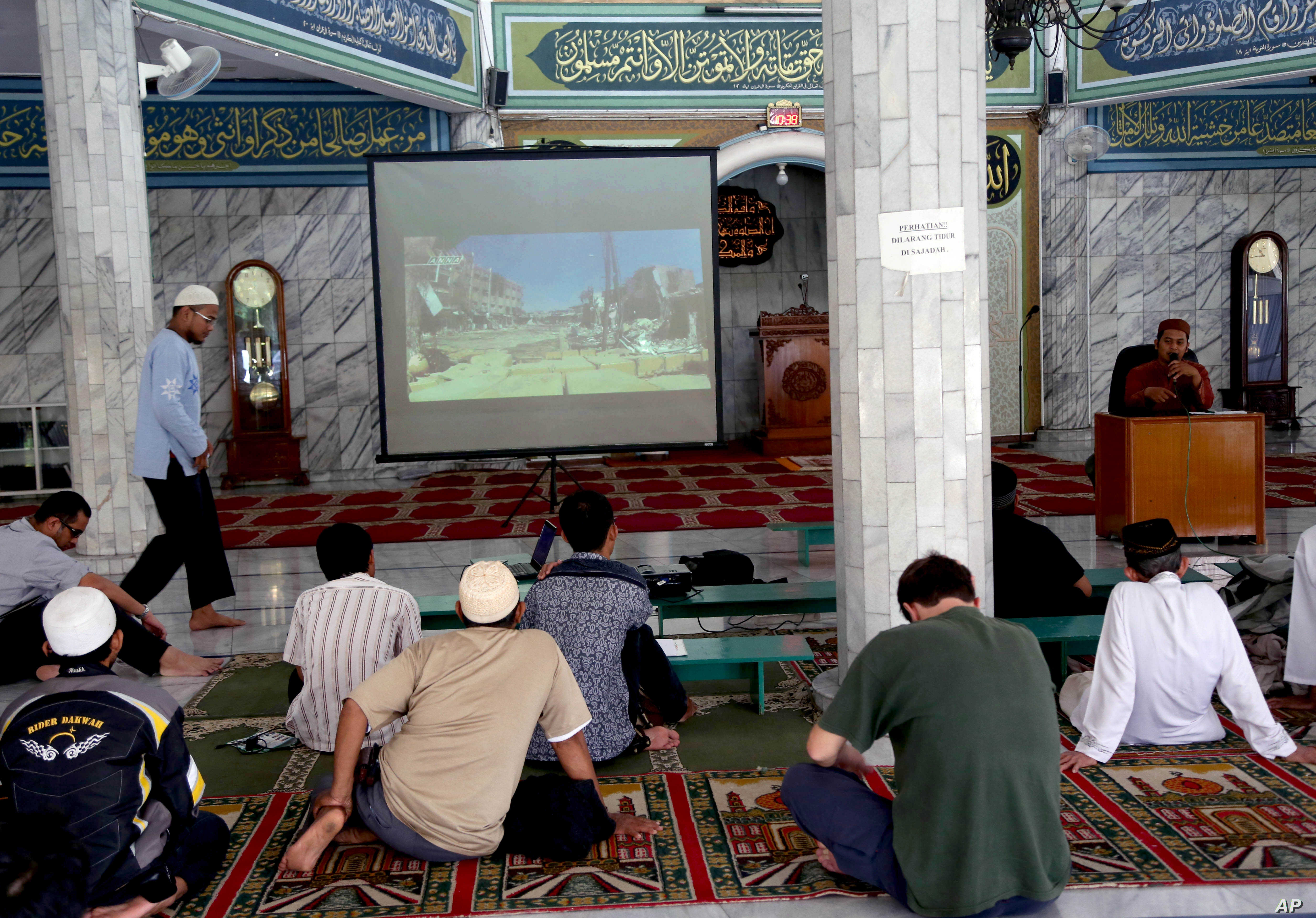 FILE - Muslim men watch a slideshow of pictures believed to be from Syria during a prayer calling for jihad to Syria at a mosque in Jakarta, Indonesia, Dec. 15, 2013.