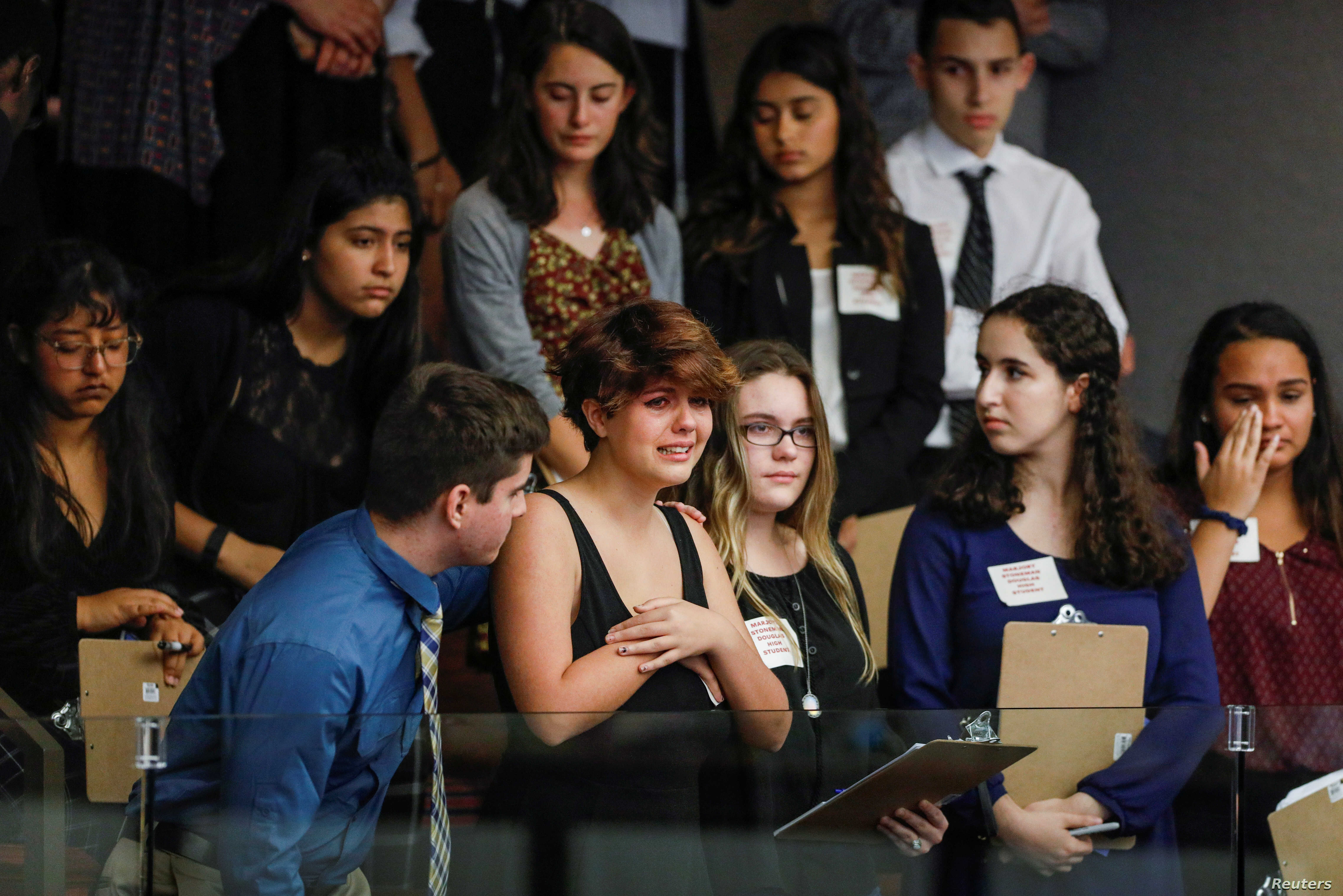 Students from Marjory Stoneman Douglas High School and those supporting them react, Feb. 20, 2018, as they watch the Florida House of Representatives vote down a procedural move to take a bill banning assault weapons out of committee and bring it to ...
