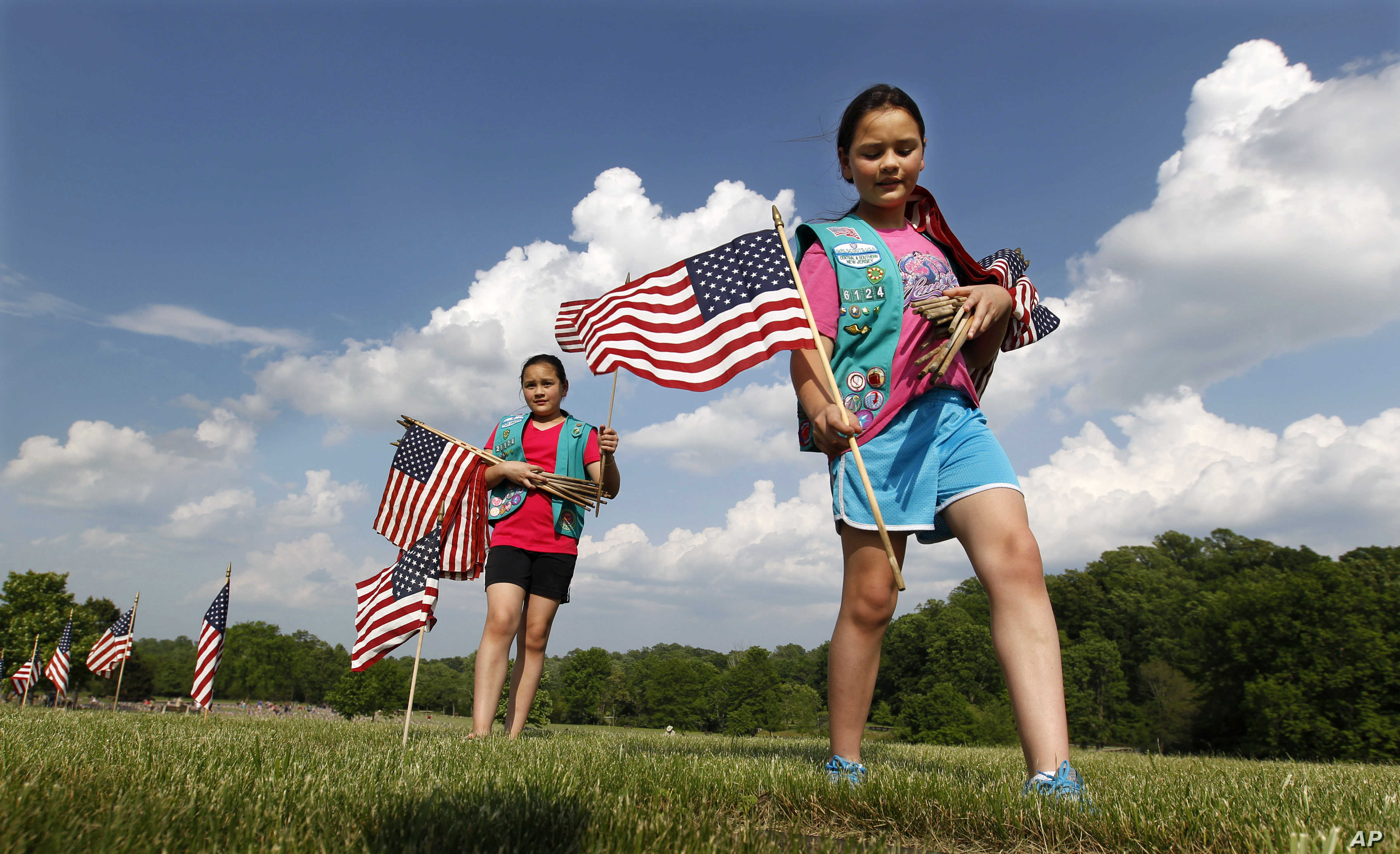 Girl Scouts Sarah and Megan Lontoc, 10, place flags as the scouts placed thousands of flags on veteran's graves at Brig. Gen. William C. Doyle Veterans Memorial Cemetery in honor of Memorial Day, Friday, May 27, 2016, in Wrightstown N.J. (AP Photo)