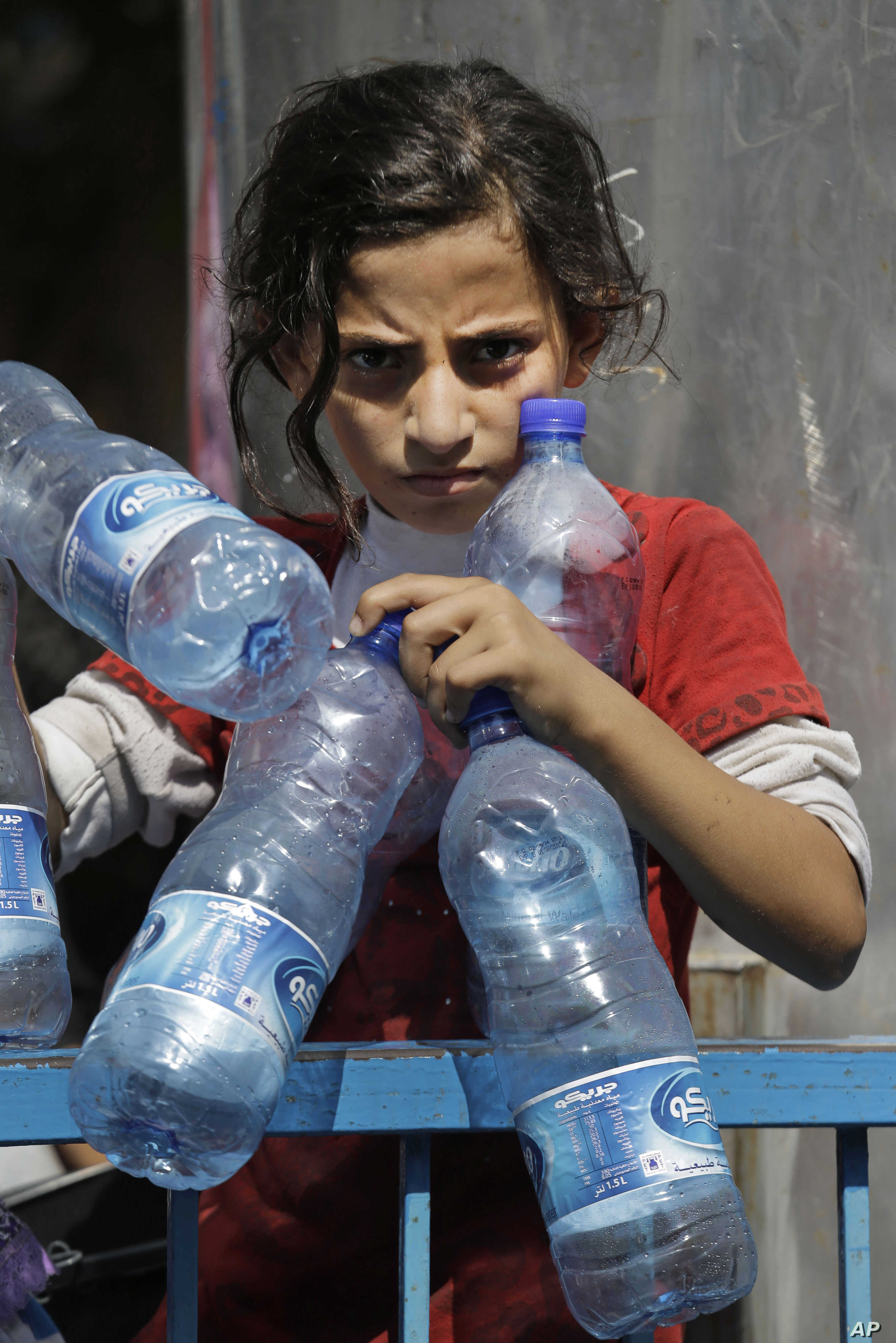 Palestinian Naama Al Attar, 13, waits to collect water at a U.N. school in Gaza City on Aug. 8, 2014.