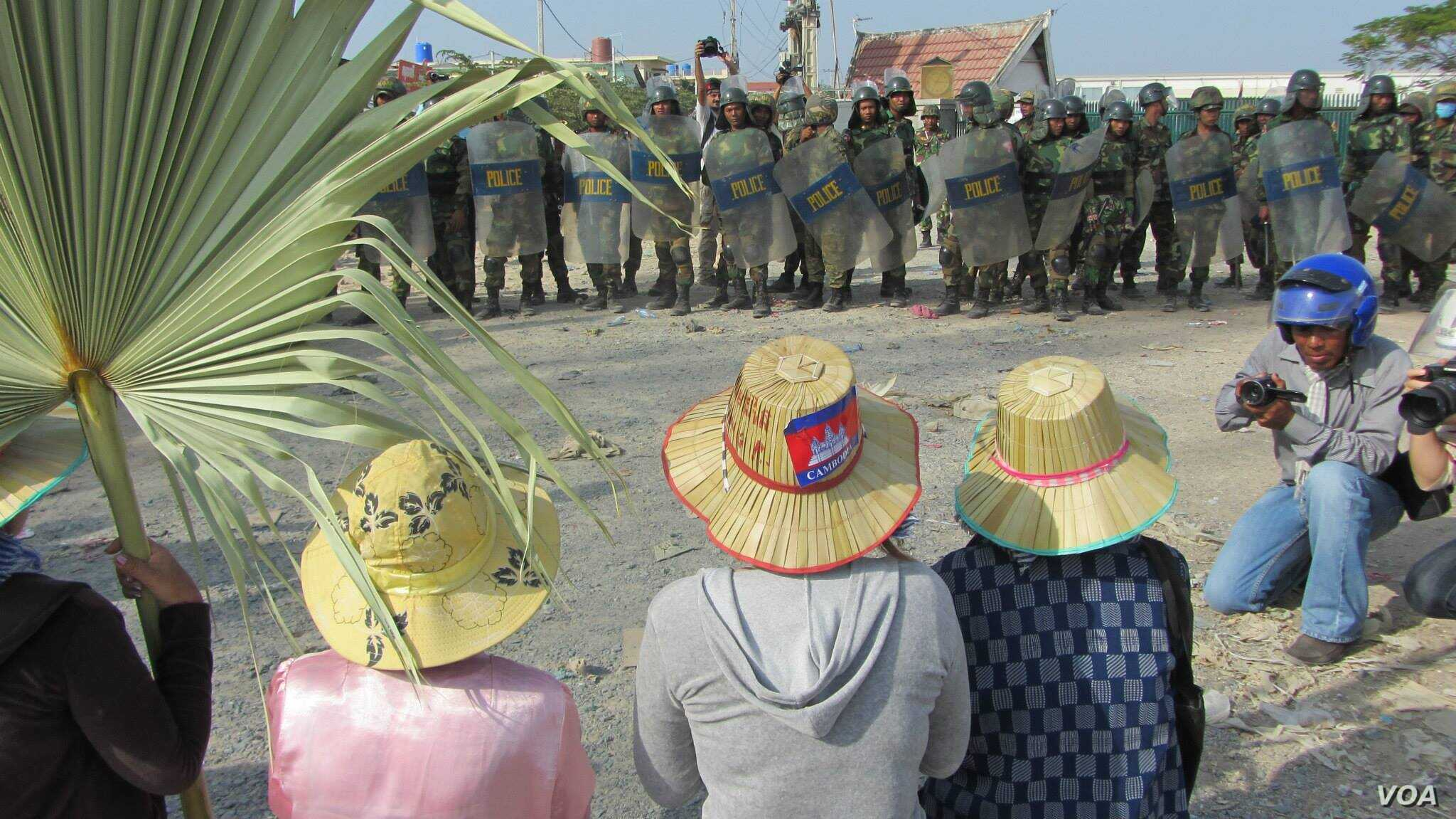 Striking garment workers are seen in front of police in Phnom Penh, Jan. 2, 2014. (VOA Khmer)