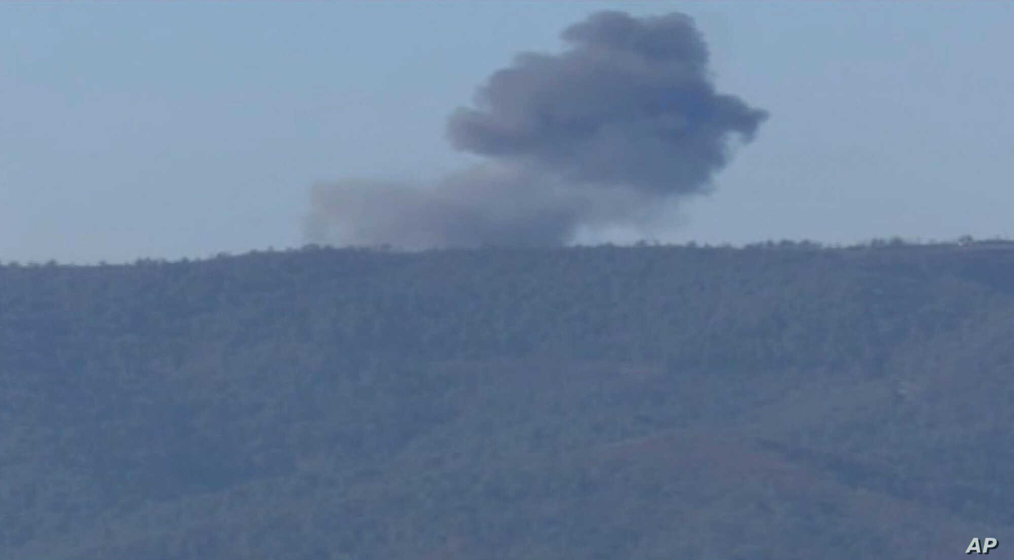 This frame grab from video by Haberturk TV, shows smoke from a Russian warplane after crashing on a hill as seen from Hatay province, Turkey, Nov. 24, 2015.