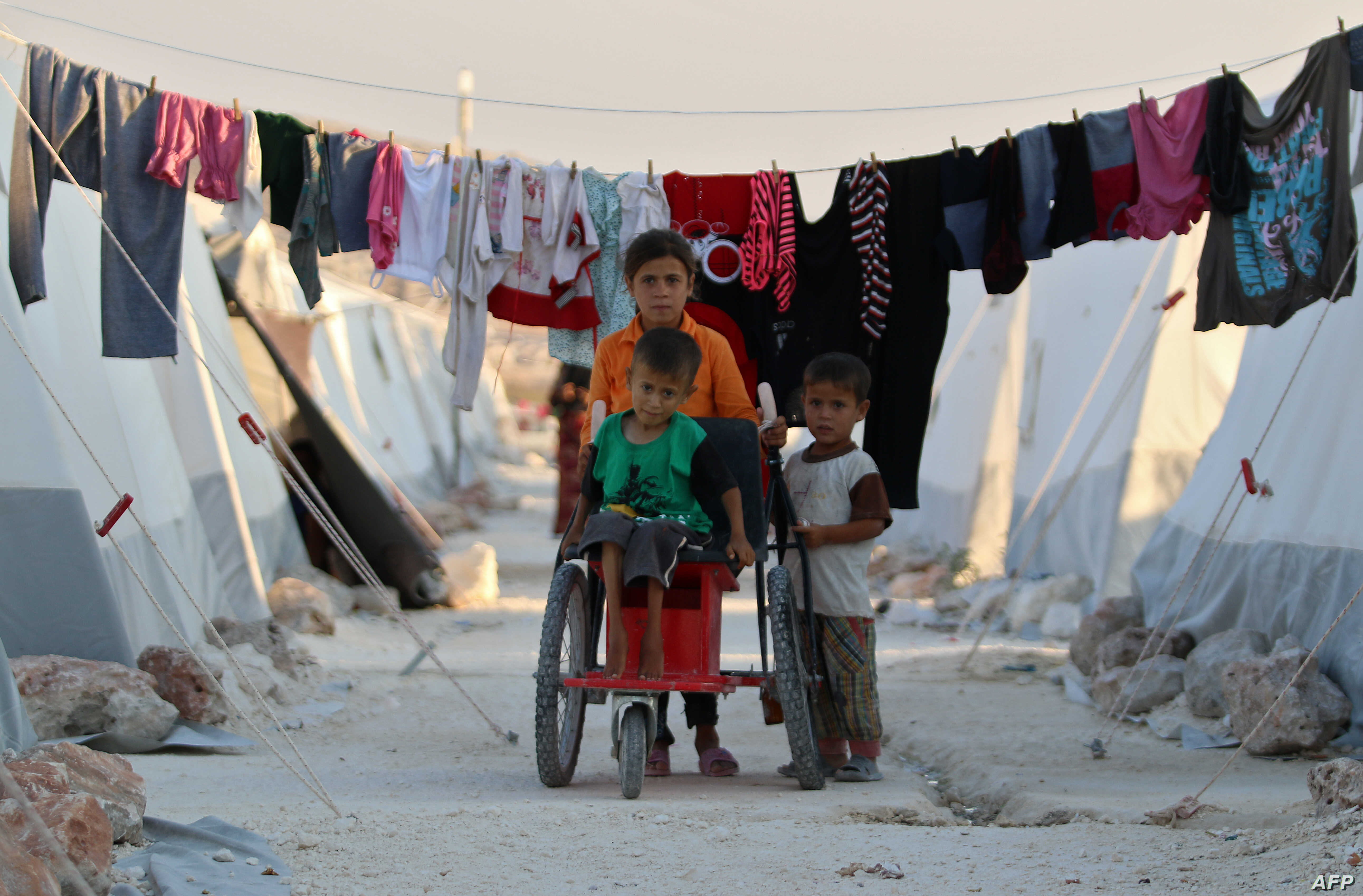 Displaced Syrian children push a boy with disability on makeshift wheelchair at a camp for displaced people in the northern Idlib province, Aug. 29, 2018.