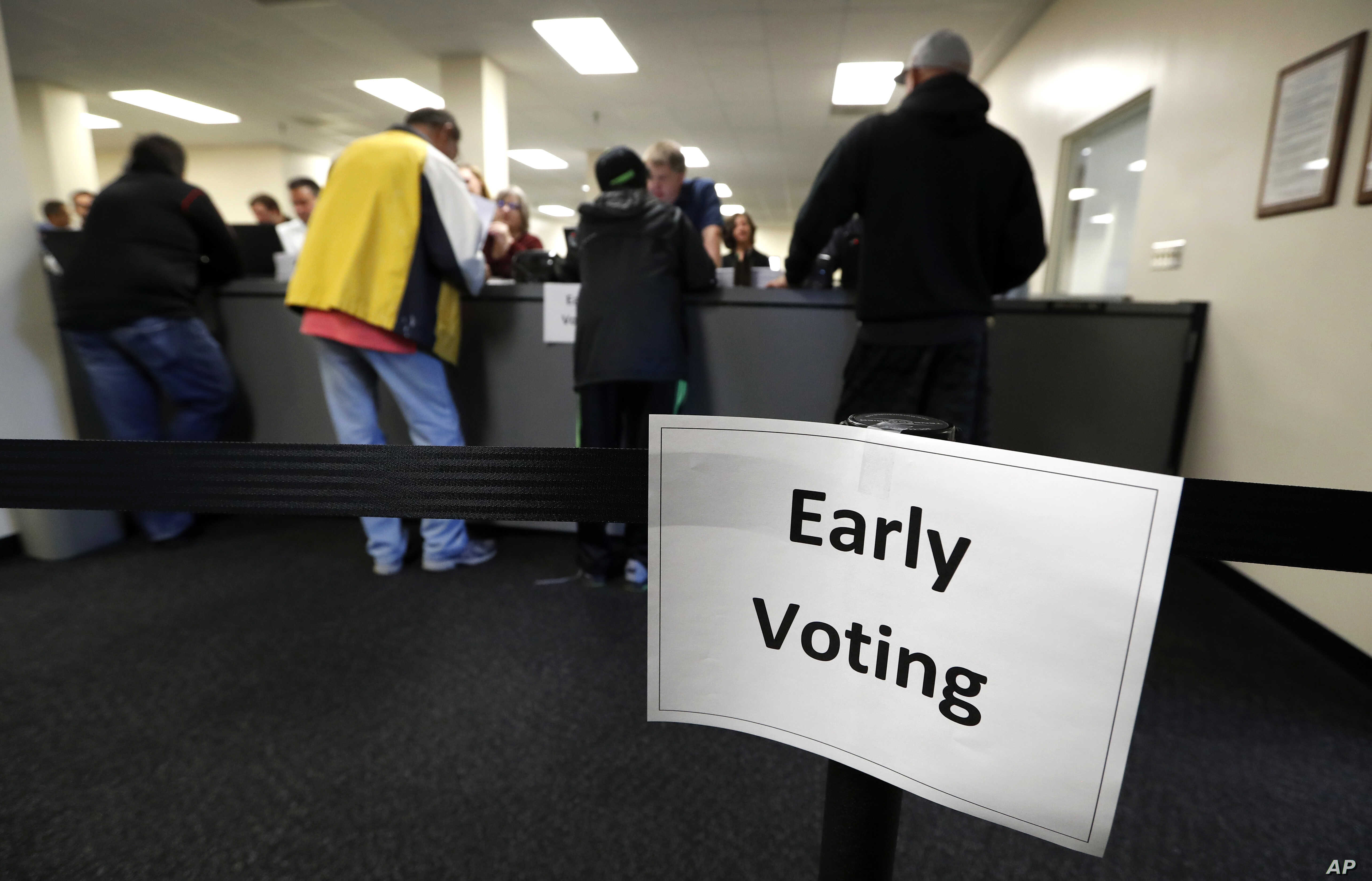 FILE -  local residents receive their ballots at the Polk County Election Office on the first day of early voting in Des Moines, Iowa.