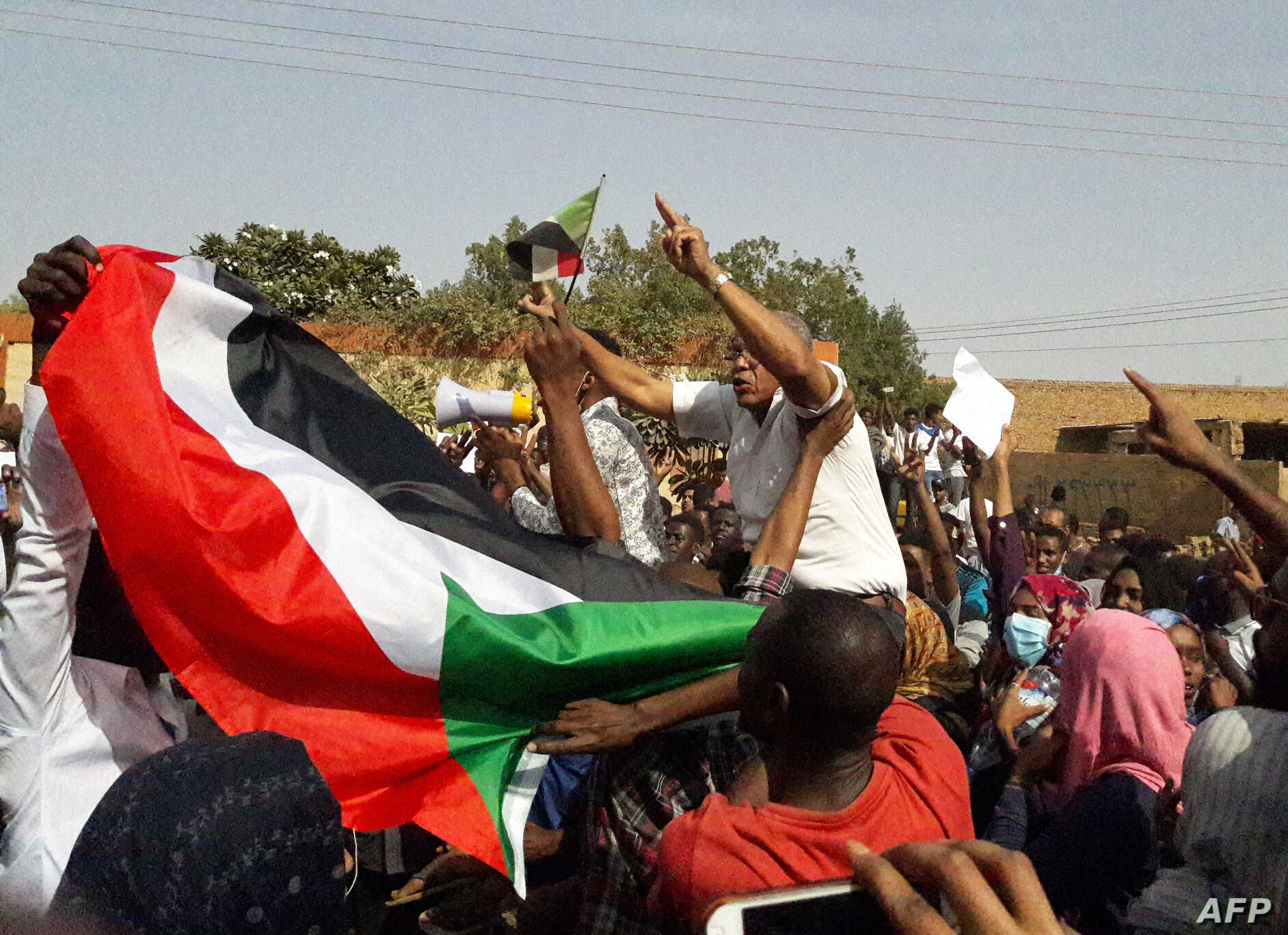 Sudanese protesters wave their national flag and chant slogans during an anti-government demonstration in the capital Khartoum's twin city of Omdurman on Jan. 31, 2019.