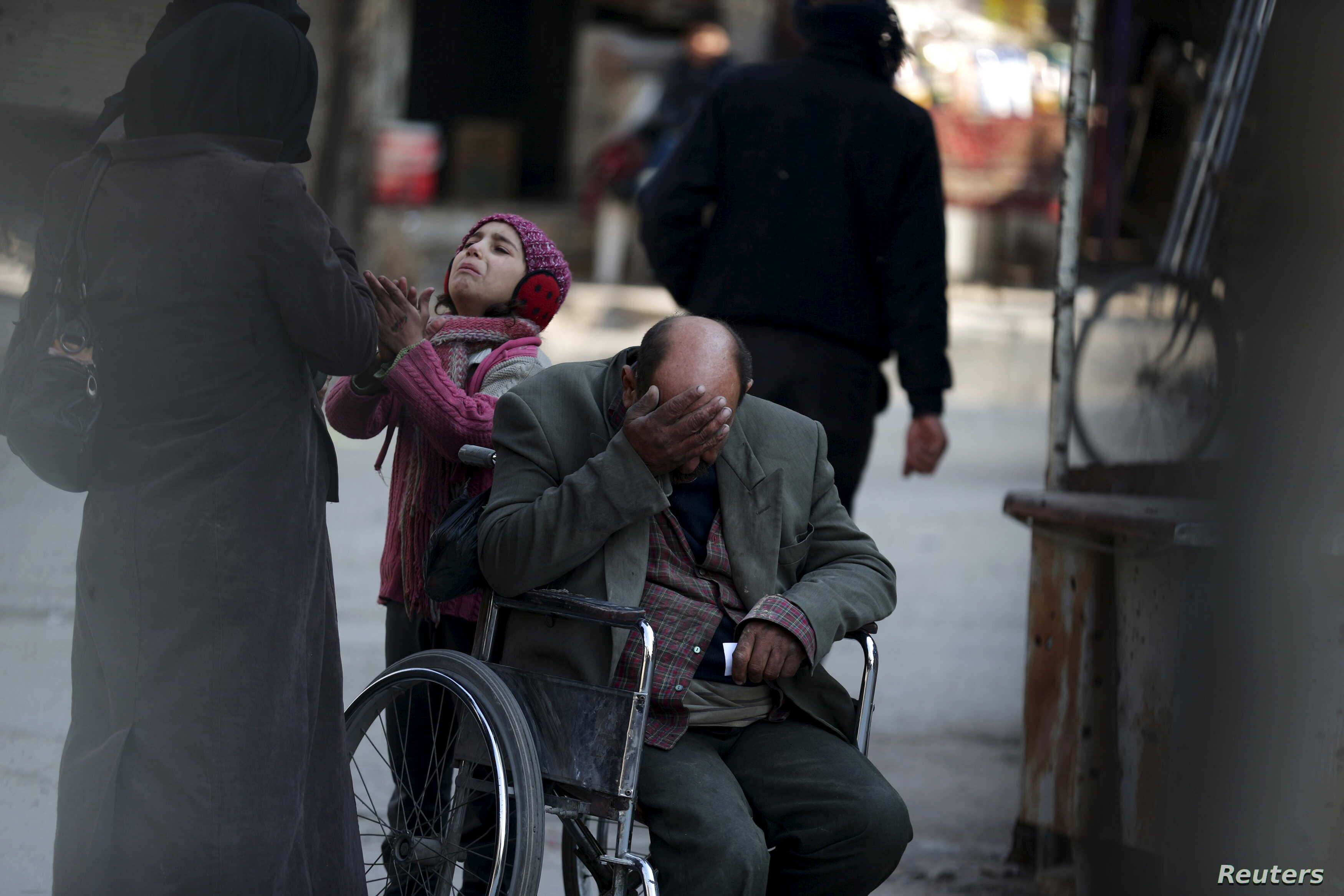 A girl with her father in a wheelchair asks for help from passers-by to pay a medical bill, in Douma, Syria, Feb. 3, 2016.