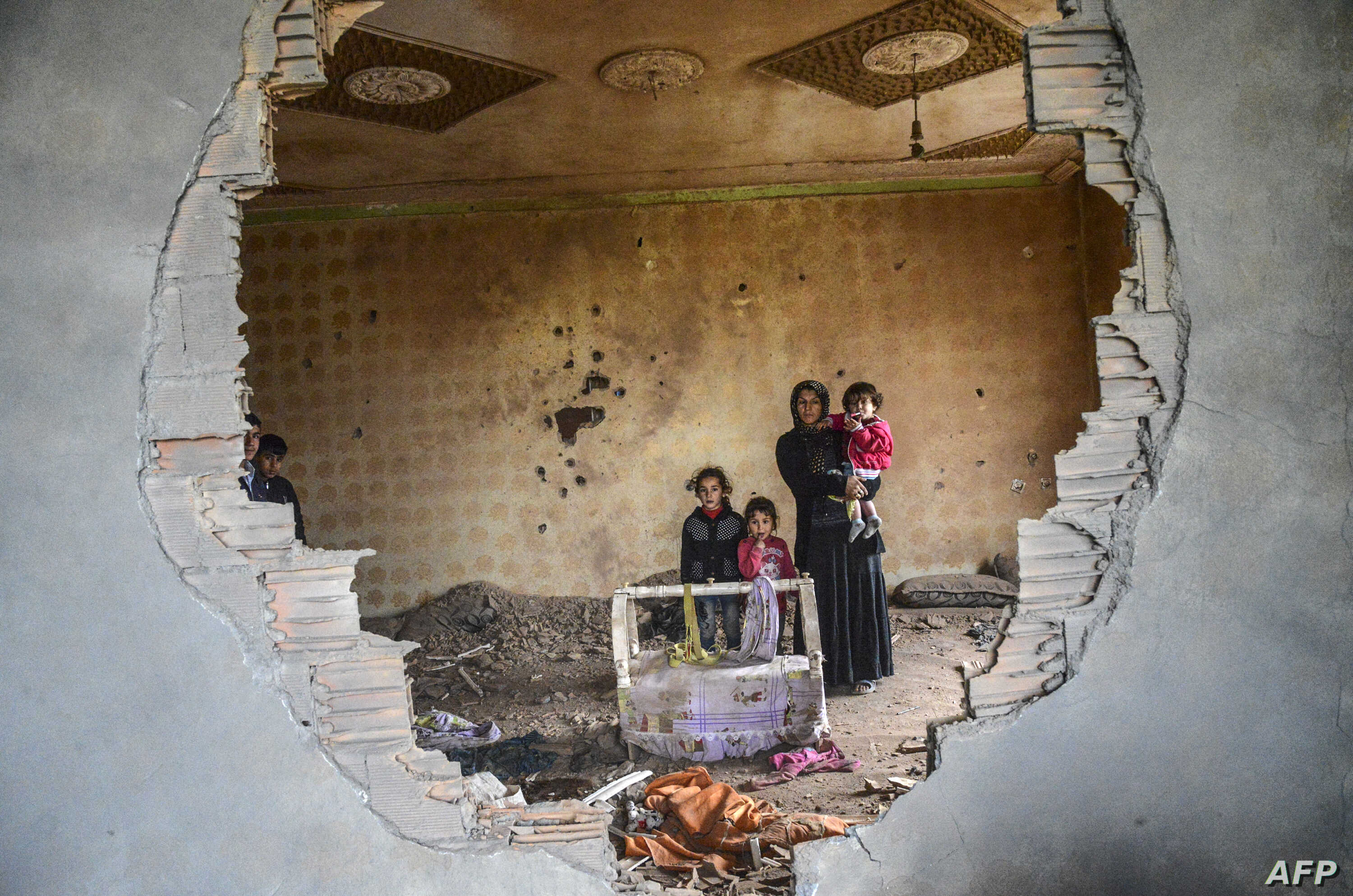 A women and her children stand in the ruins of battle-damaged house in the Kurdish town of Silopi, in southeastern Turkey, near the border with Iraq on January 19, 2016.