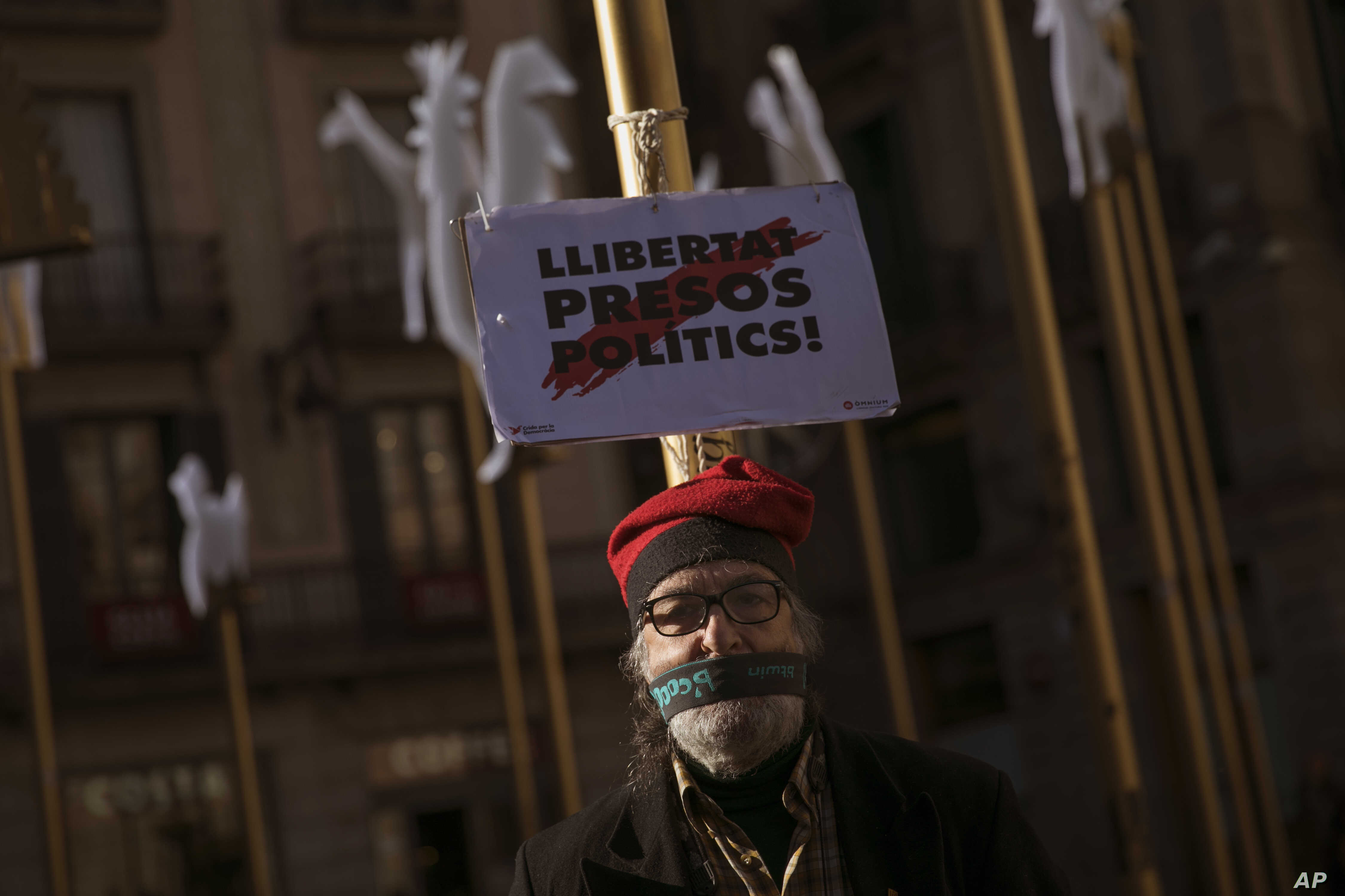 """A man stands next to a banner reading in Catalan: """"Freedom for Political Prisoners"""", in support of Catalonia politicians who have been jailed on charges of sedition in Barcelona, Spain, Dec. 19, 2017."""