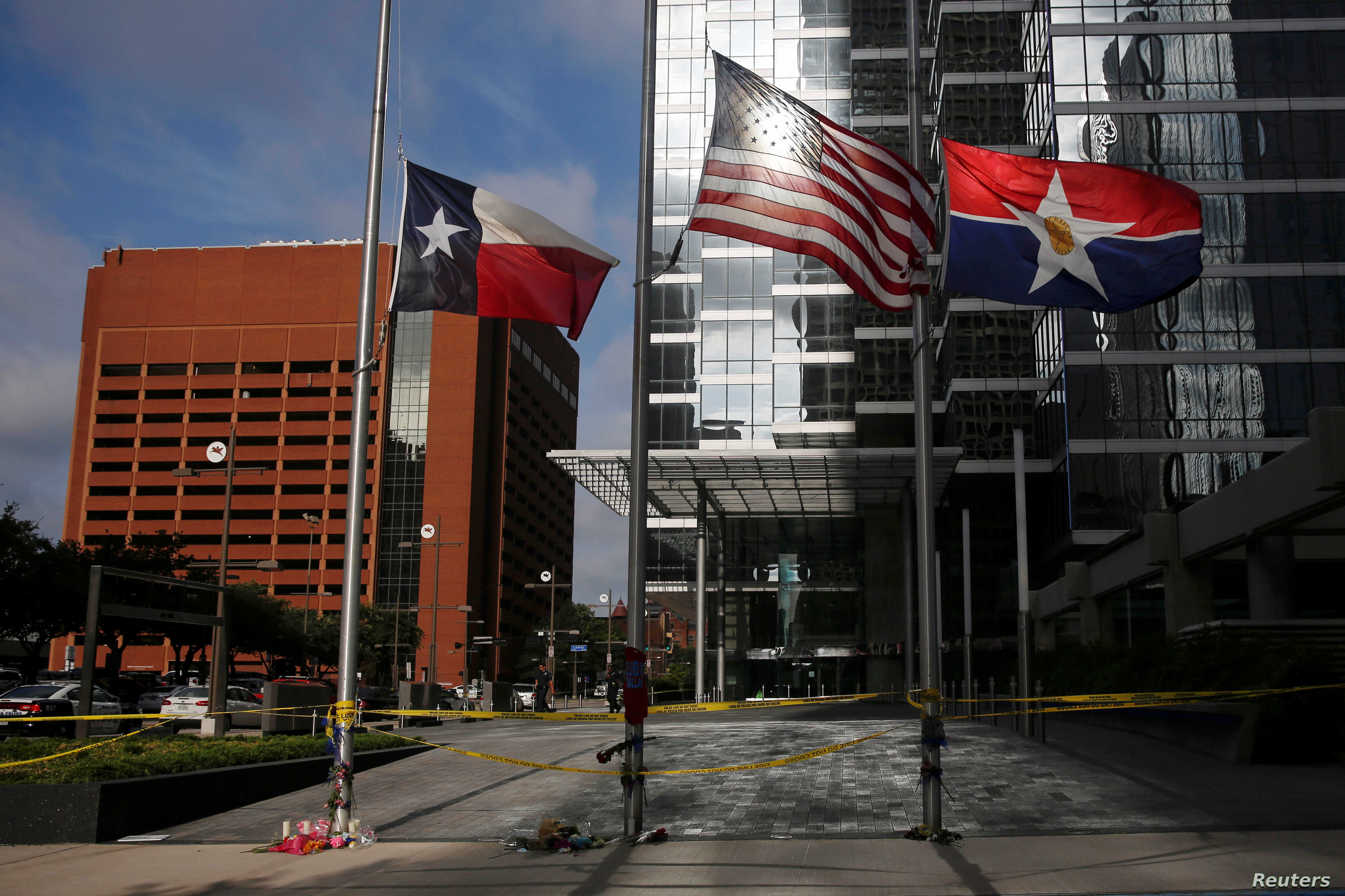 Flags fly at half-staff at a makeshift memorial near the crime scene two days after a gunman ambushed and killed five police officers at a protest decrying police shootings of black men, in Dallas, July 9, 2016.