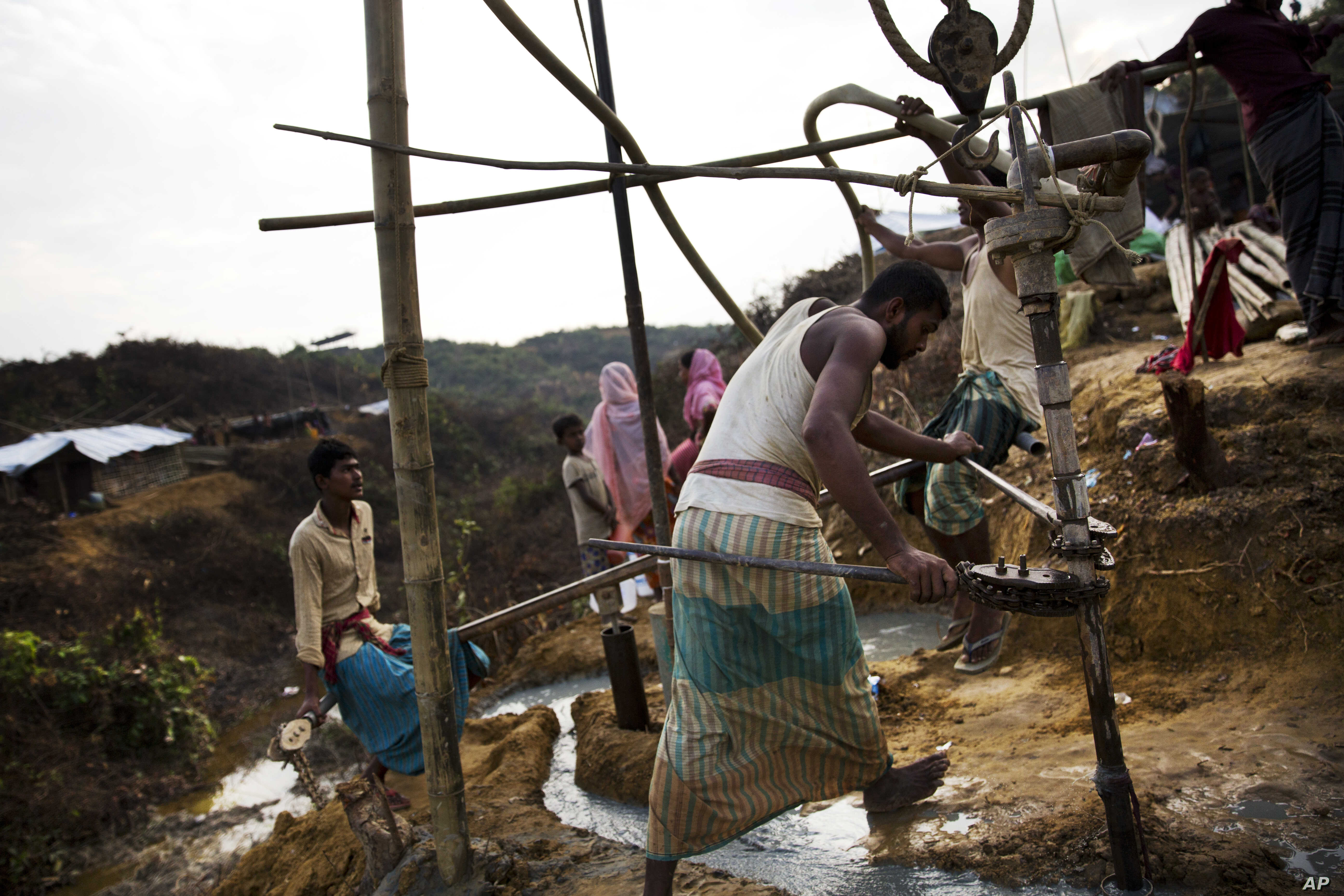 FILE - Bangladeshi laborers build a tube well in a Rohingya refugee camp, in Cox's Bazar, Bangladesh, Oct. 29 2017.